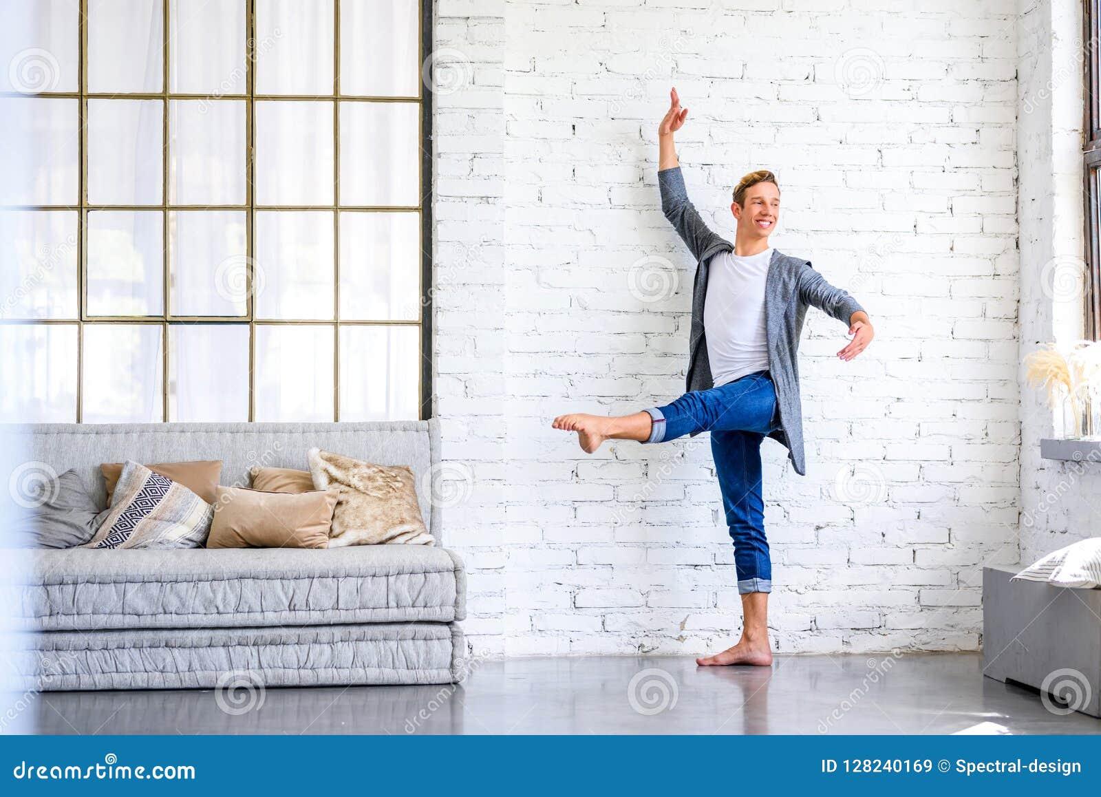 Un giovane ballerino di balletto maschio bello che pratica in uno stile A del sottotetto