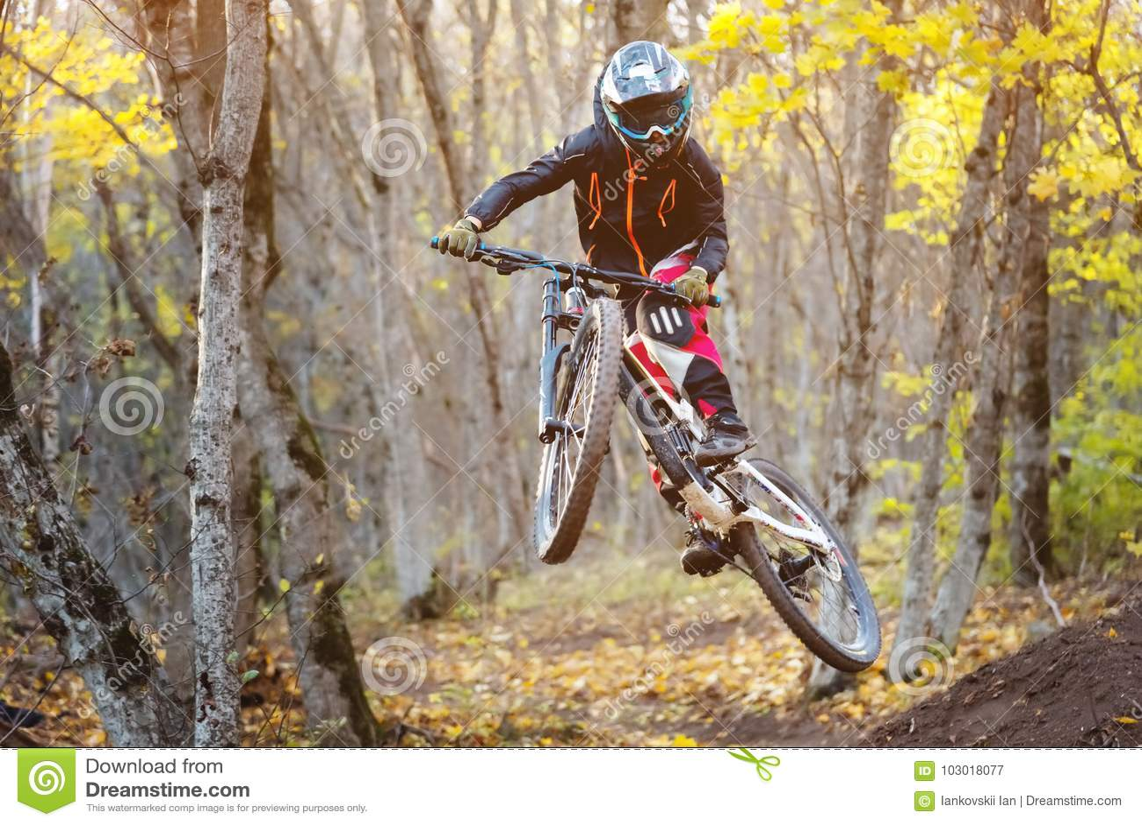 Un giovane cavaliere alla ruota del suo mountain bike fa un trucco nel salto sul trampolino della montagna in discesa