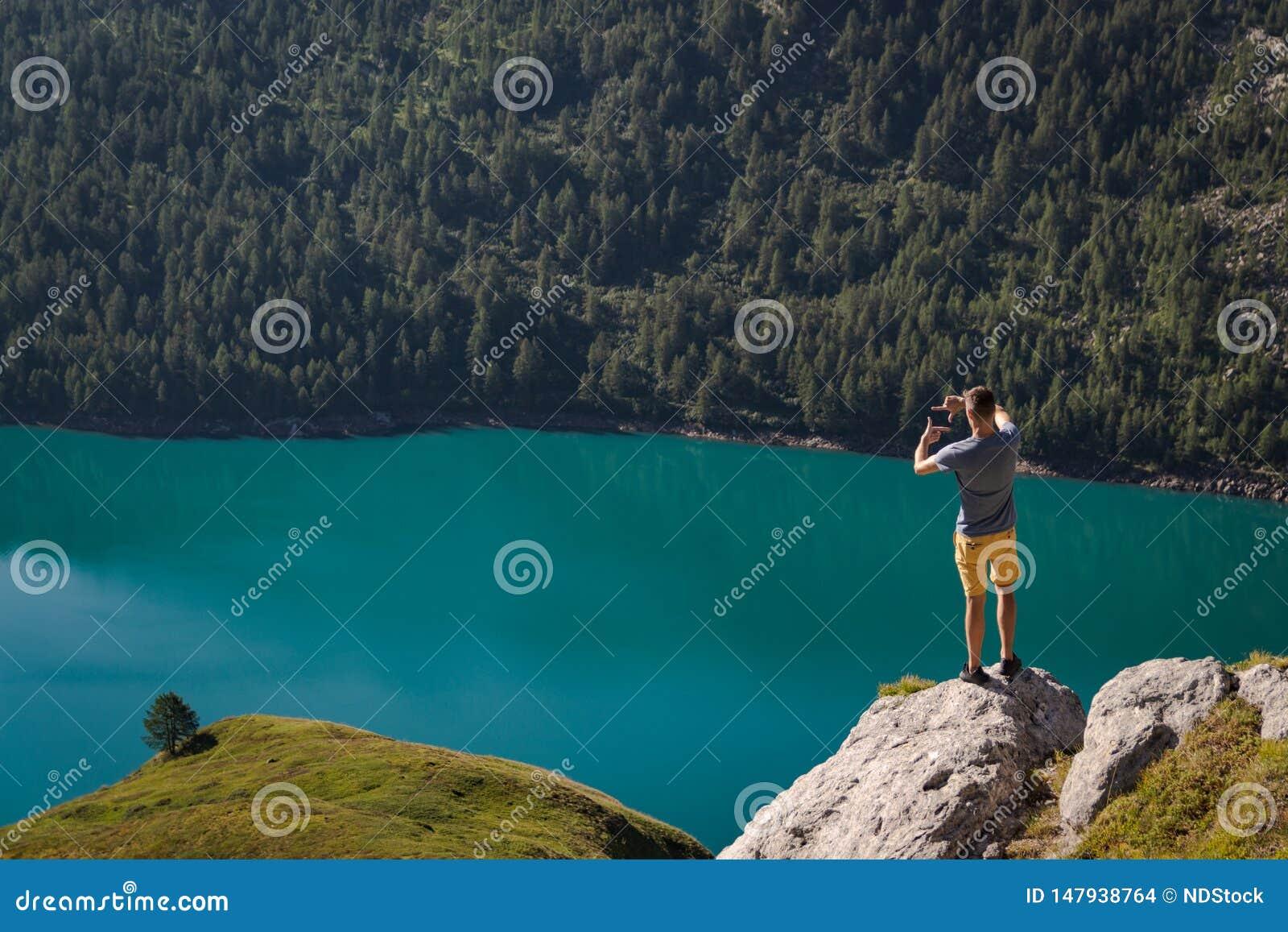 Un giovane che incornicia un albero con le sue mani Ritom del lago come fondo