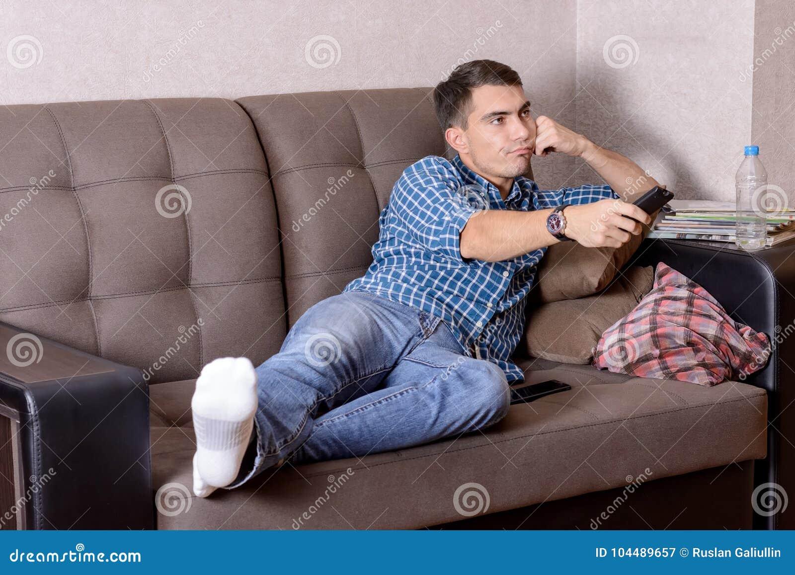 Un giovane in jeans, con un telecomando per la noia della TV sul fronte cambia il canale