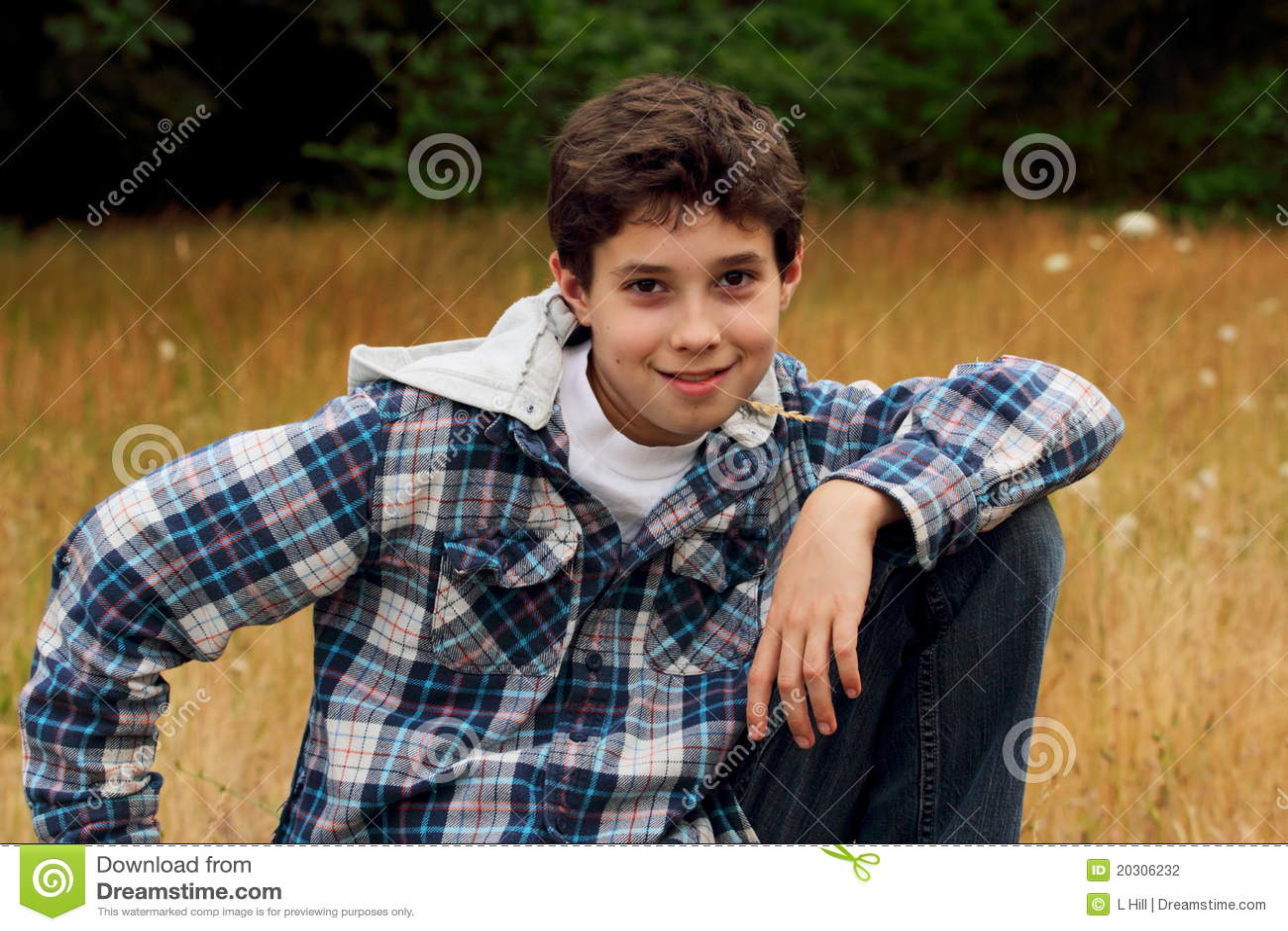 Un giovane ragazzo di paese del preteen che si siede in un campo di ...
