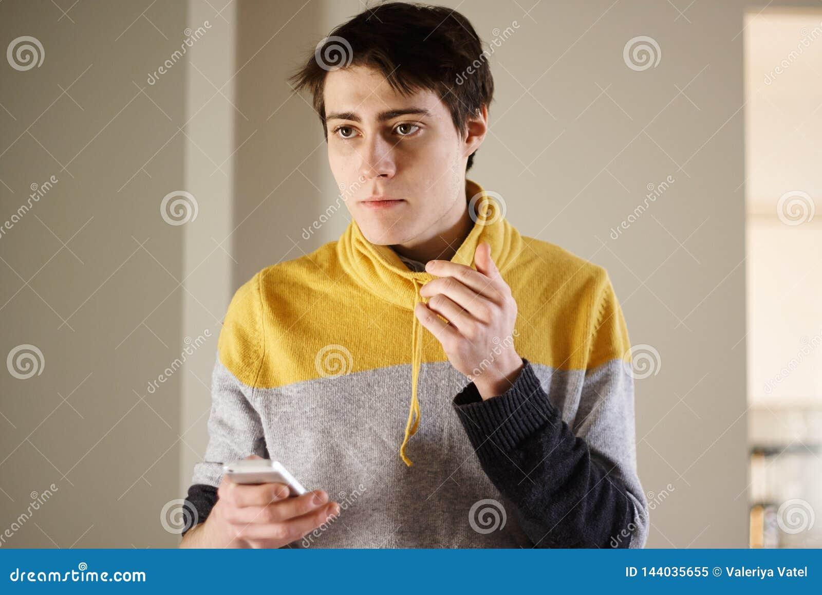 Un giovane tipo bello in un maglione giallo tiene meditatamente un telefono nelle suoi mani e sguardi al lato