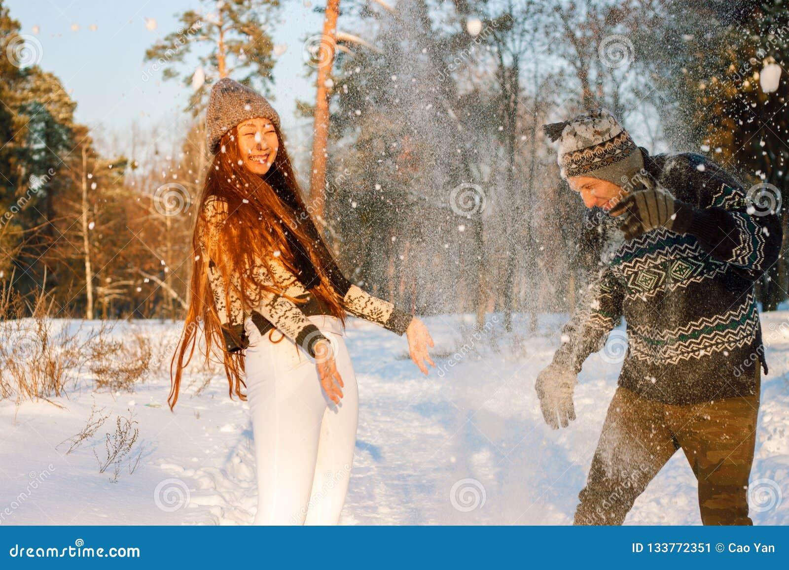 Un giovane uomo bello dell aspetto europeo e una giovane ragazza asiatica in un parco sulla natura nell inverno