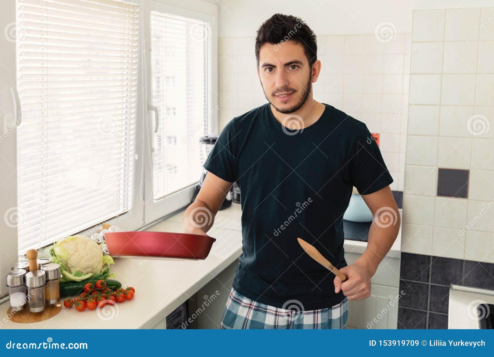 Un giovane uomo castana bello sta stando nella cucina e sta tenendo una padella in sue mani