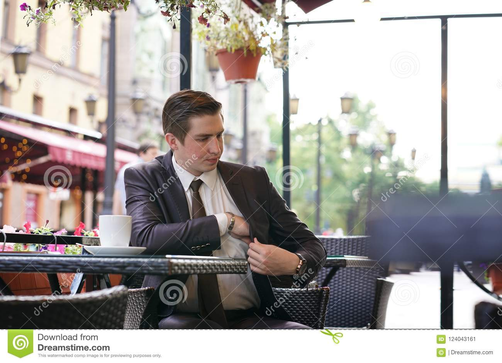 Un giovane uomo d affari è venuto a pranzare in un caffè della via, si siede ad una tavola ed estrae una borsa per pagare la fatt