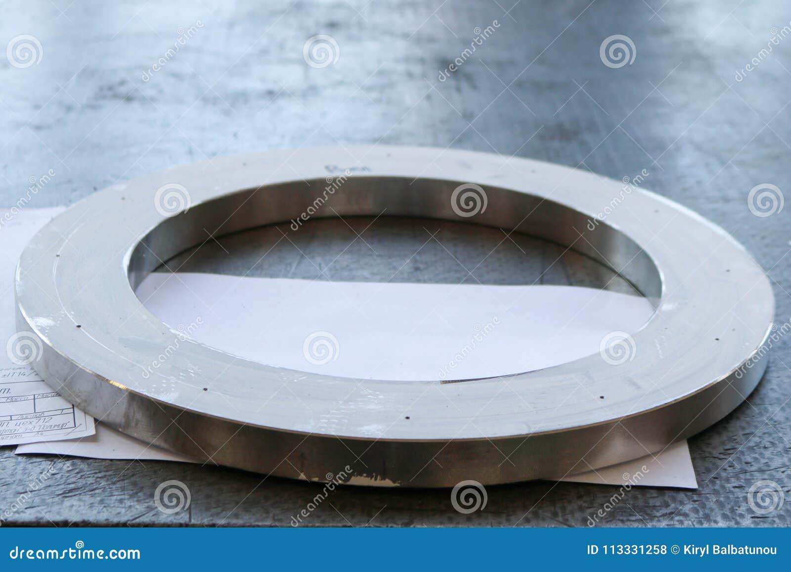Un grand anneau brillant rond en métal avec de petits trous, trous, une bride sur la table fonctionnante de fer dans l usine, l a
