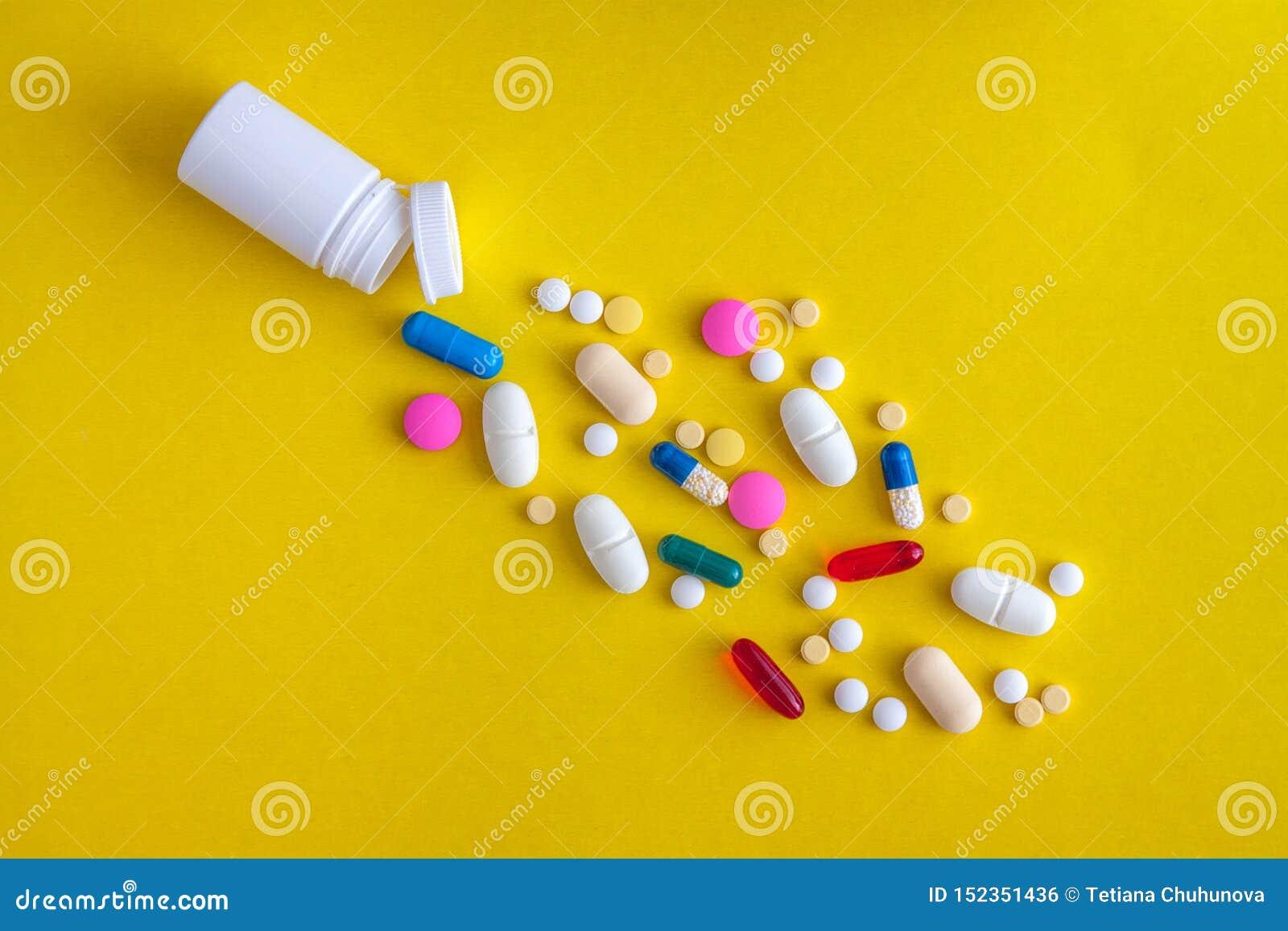 Un grand choix de pilules médicinales et pilules versées hors de la fiole sur un fond jaune Configuration plate Copiez l espace t