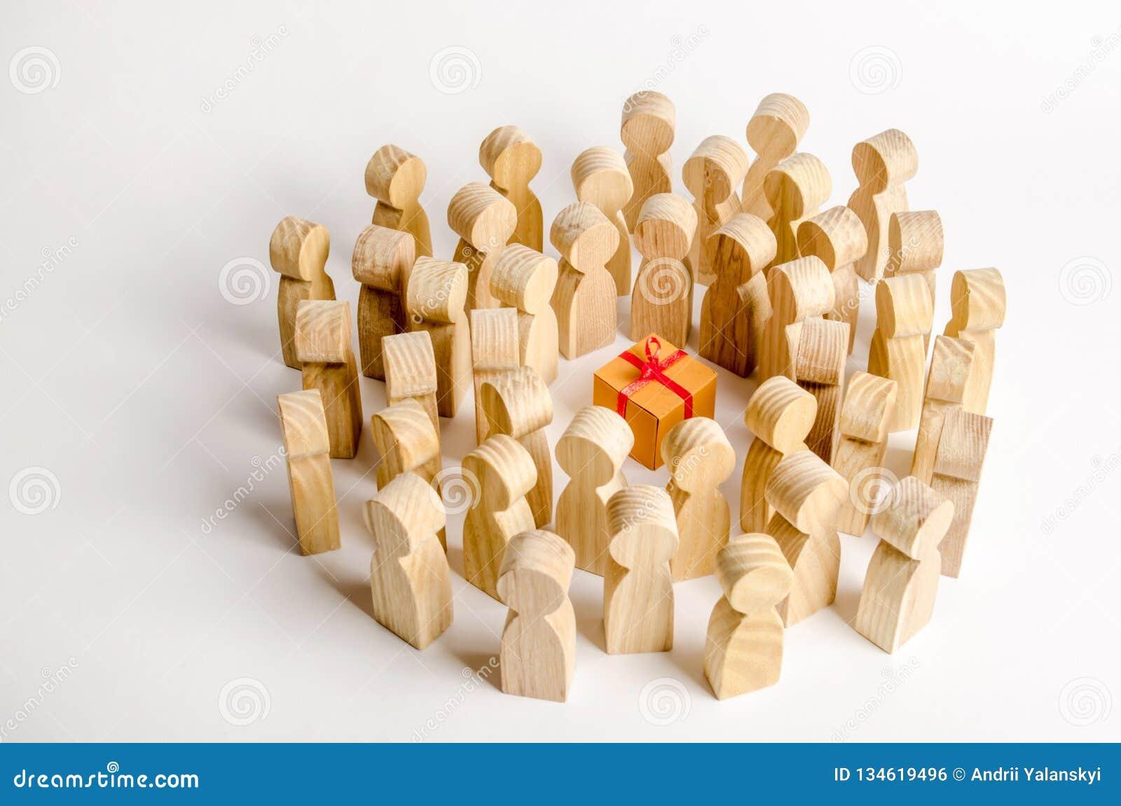 Un grand groupe de personnes entoure le boîte-cadeau Le concept de choisir un bon cadeau, nombre limité, tout vendu  Un cadeau