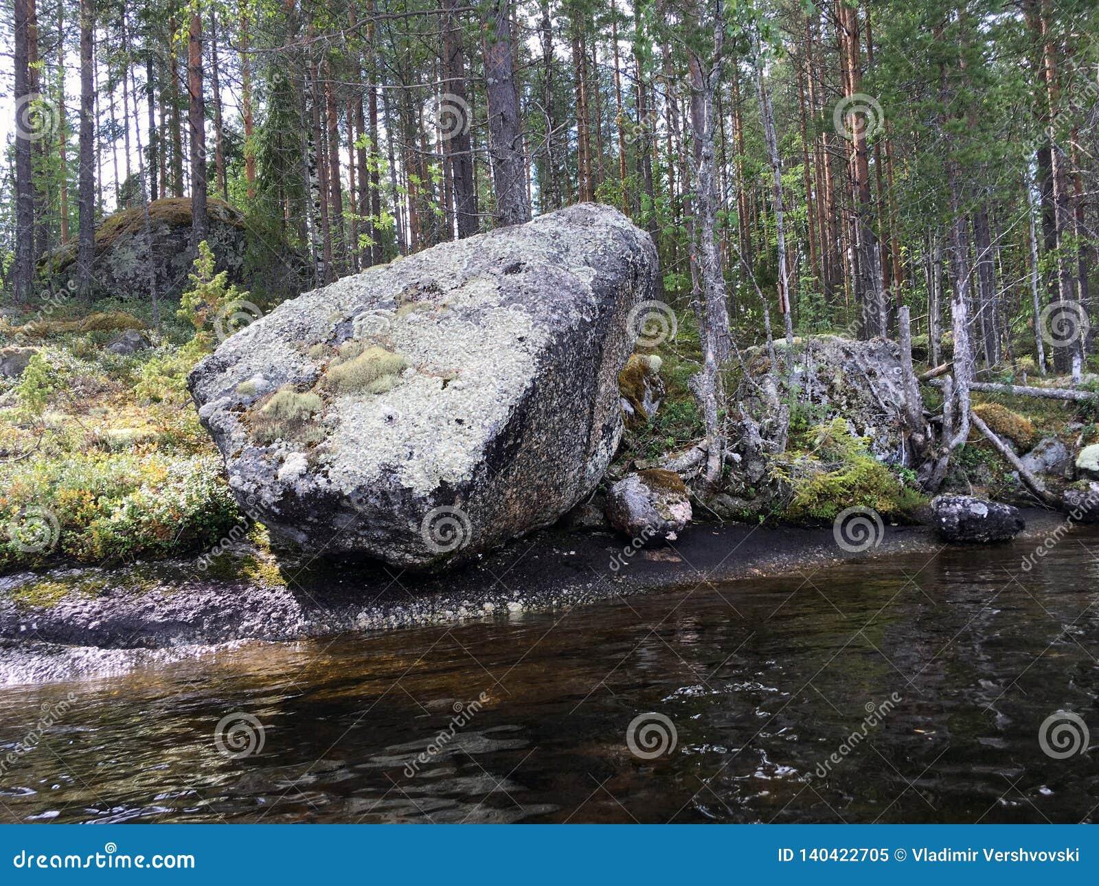 Un grand rocher sur le rivage du lac