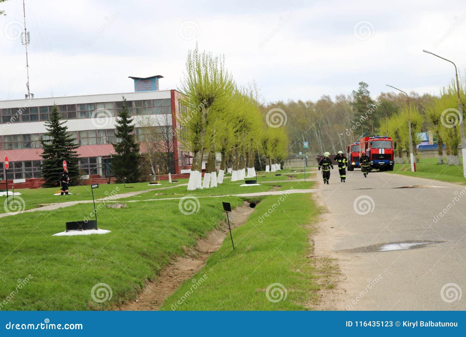 Un grand véhicule de sauvetage du feu rouge, un camion pour s éteindre un feu et des sapeurs-pompiers de mâle à un produit chimiq
