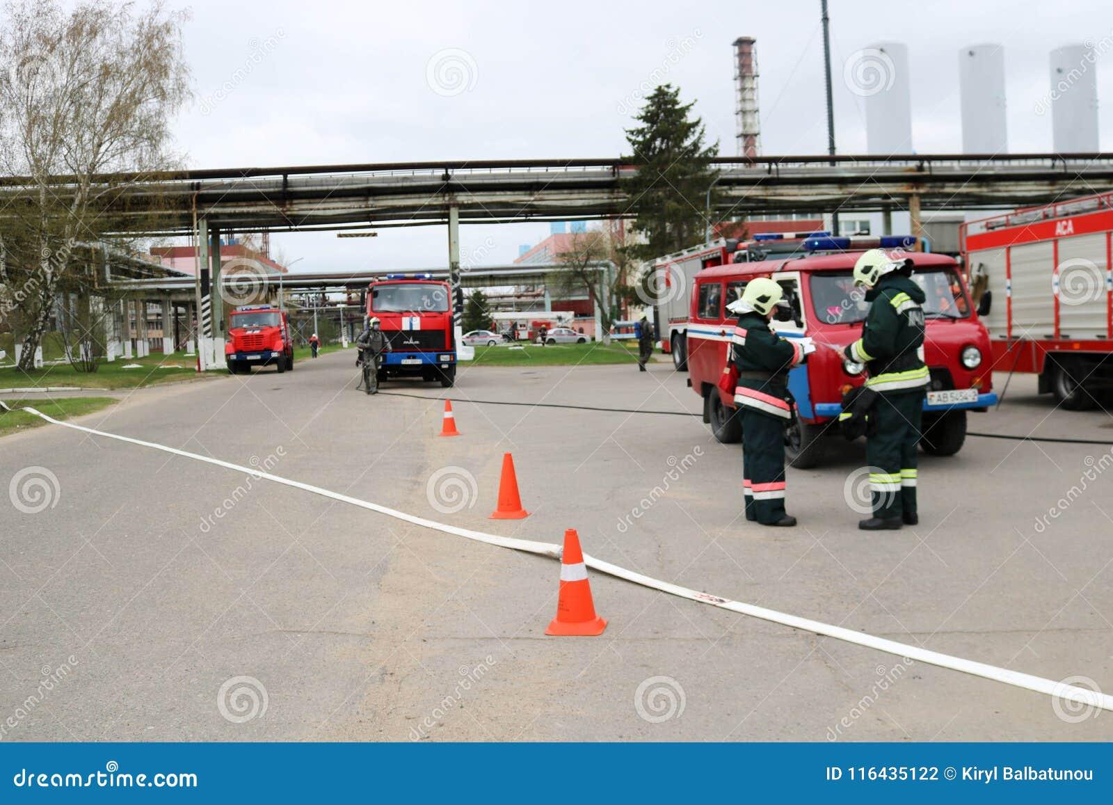 Un grand véhicule de sauvetage du feu rouge, un camion pour s éteindre un feu et des sapeurs-pompiers de mâle sont préparés pour