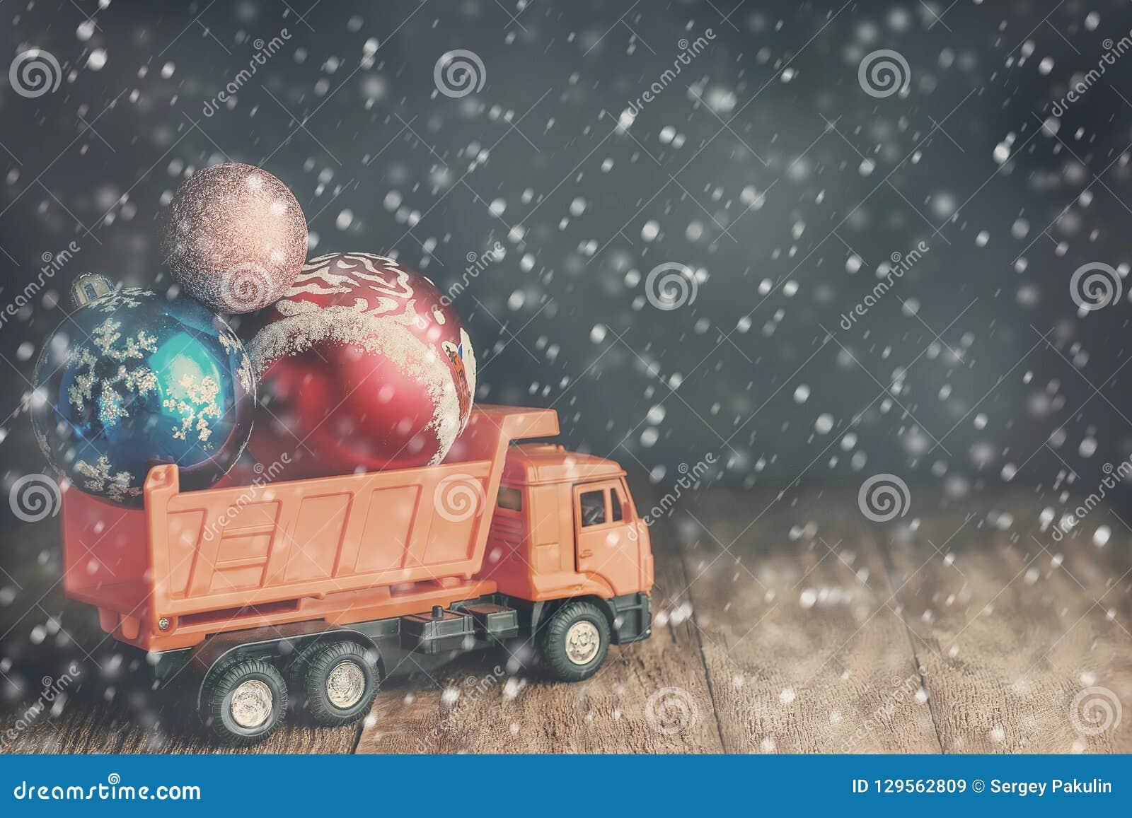 Un grande autocarro con cassone ribaltabile porta le palle di Natale durante le bufere di neve e le precipitazioni nevose