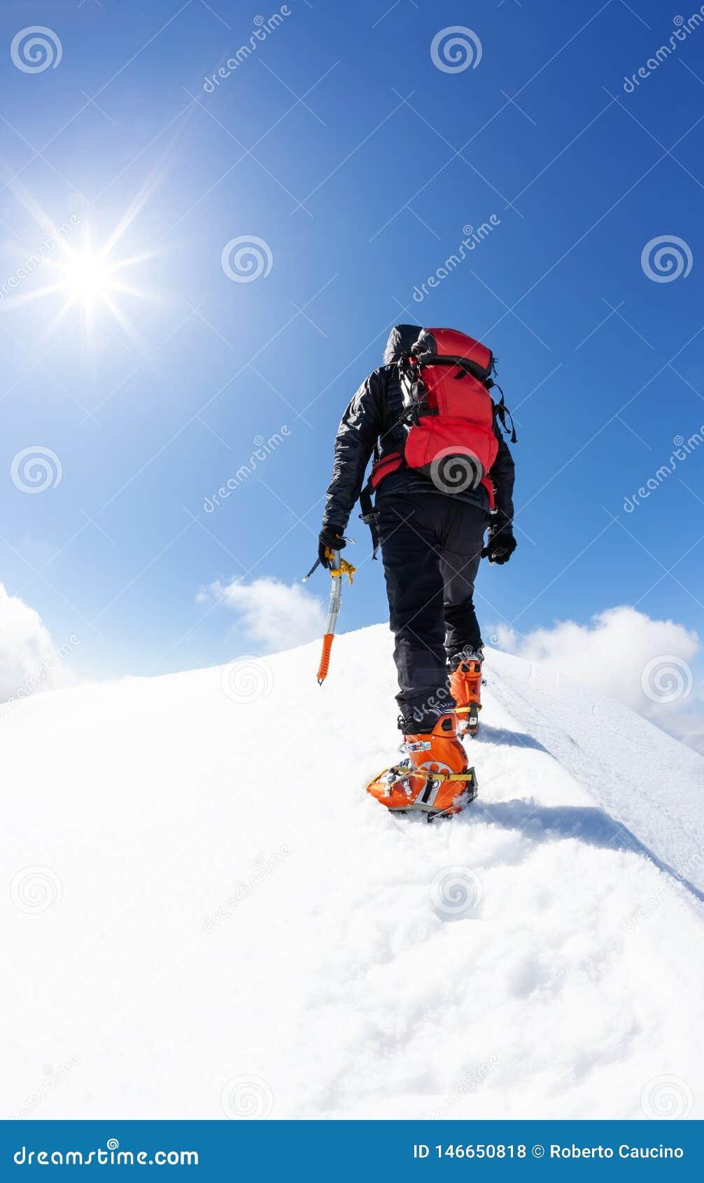 Un grimpeur atteignant le sommet d une crête de montagne neigeuse concept : surmontez l adversité, atteignez les buts