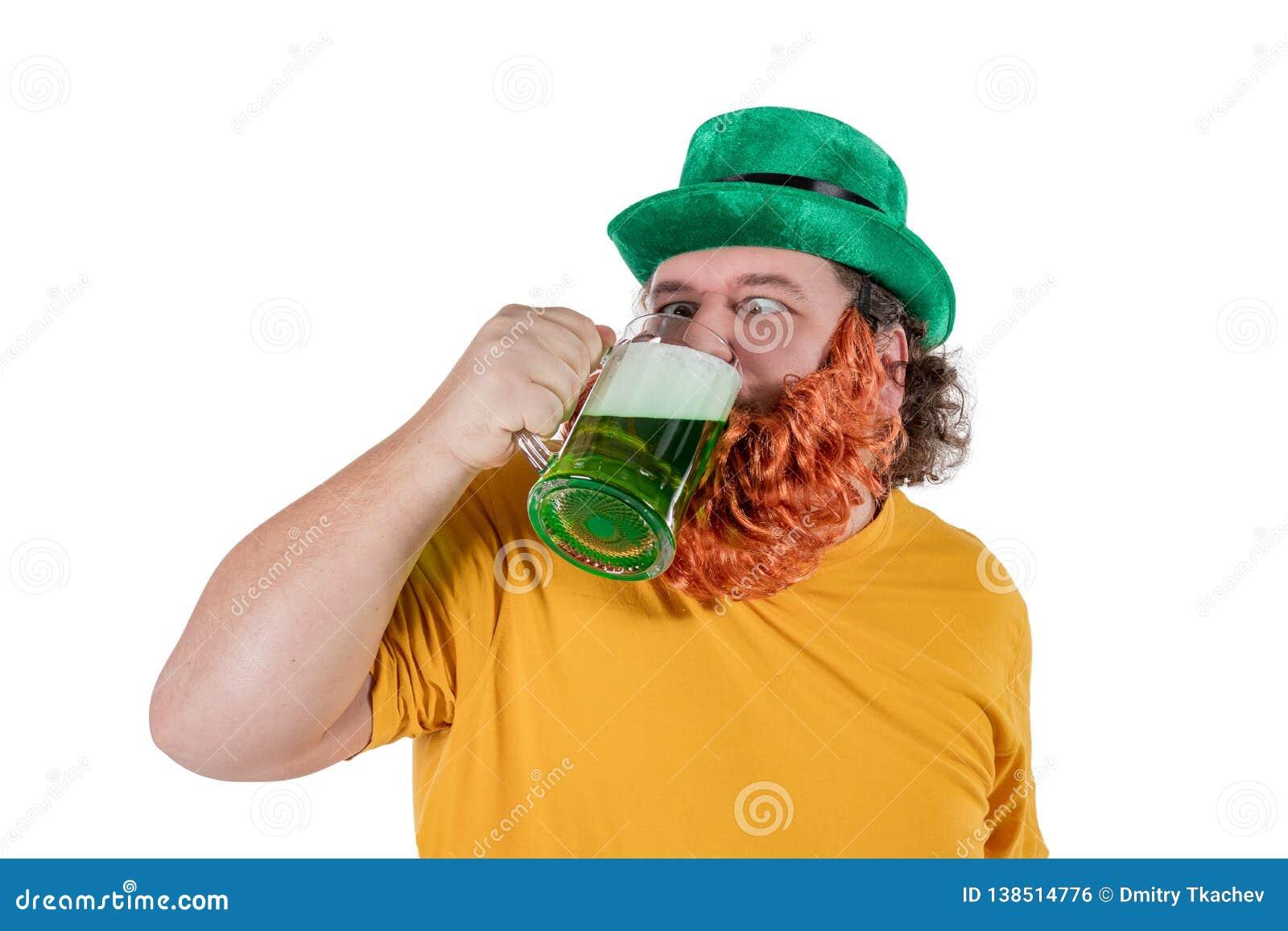 Un gros homme heureux de sourire dans un chapeau de lutin avec de la bière verte au studio Il célèbre St Patrick