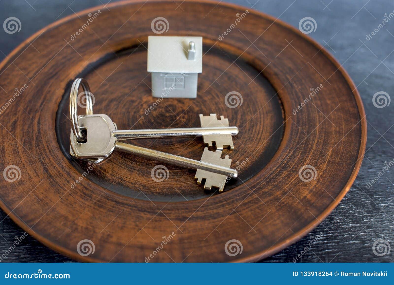 Un groupe de clés se trouvent d un plat de cru, avec une imitation de la maison sous forme de disposition en métal