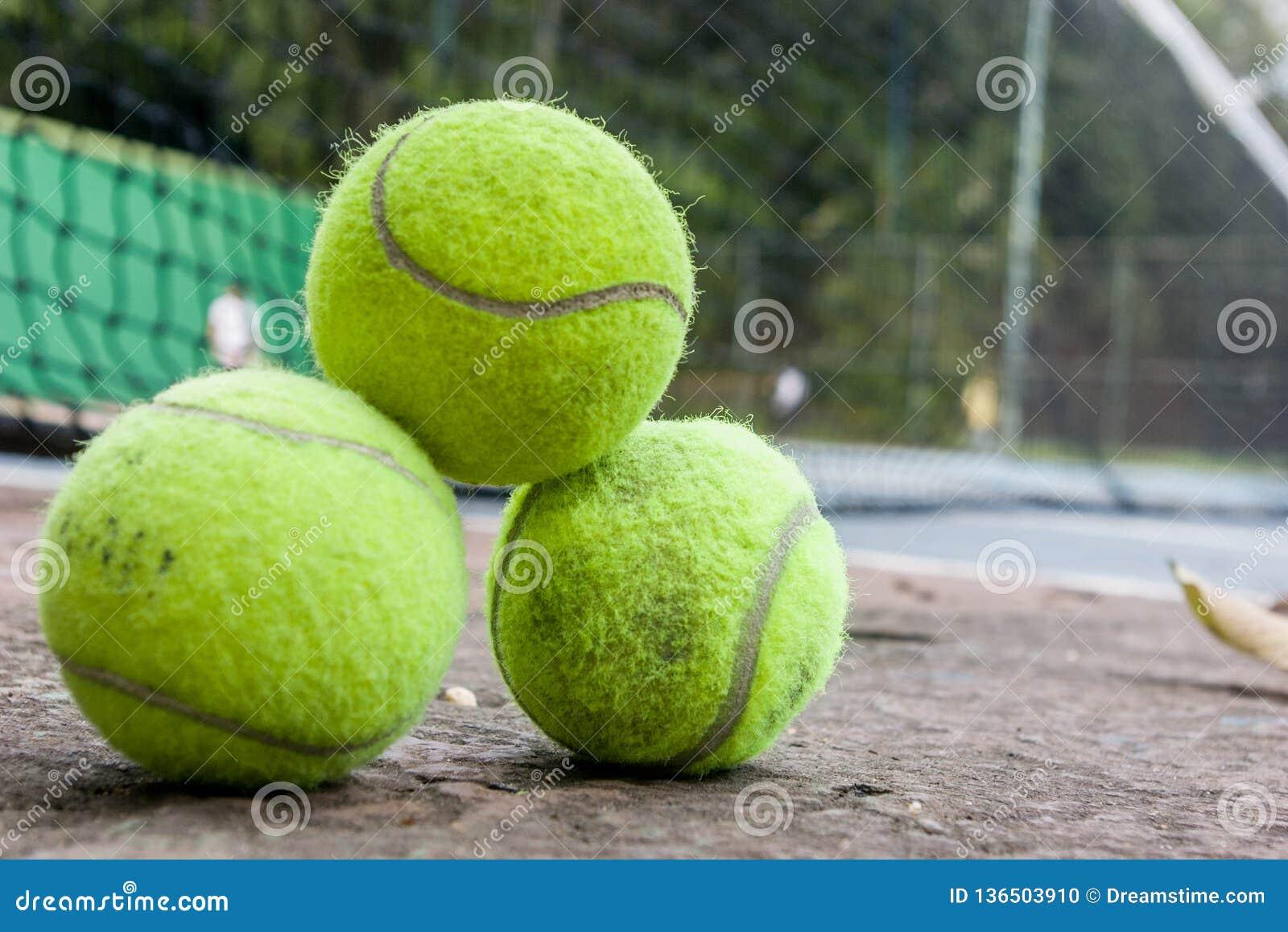 Un groupe de trois balles de tennis vertes un jour ensoleillé