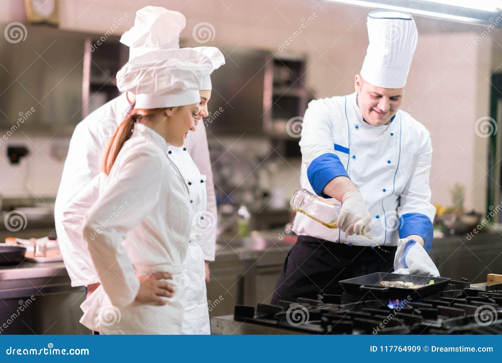 Un grupo de cocineros que preparan la comida deliciosa en alto restaurante de lujo