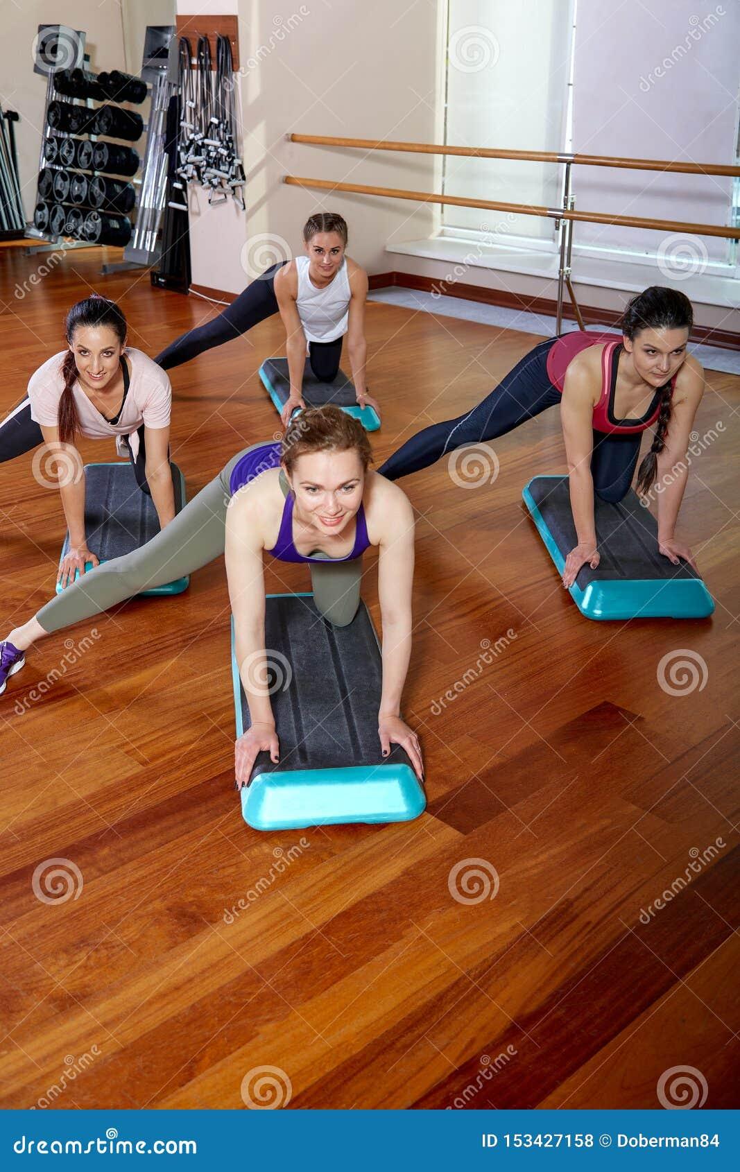 Un grupo de divertirse a gente joven en ropa de deportes, en un cuarto de la aptitud, haciendo pectorales o tablones en el gimnas