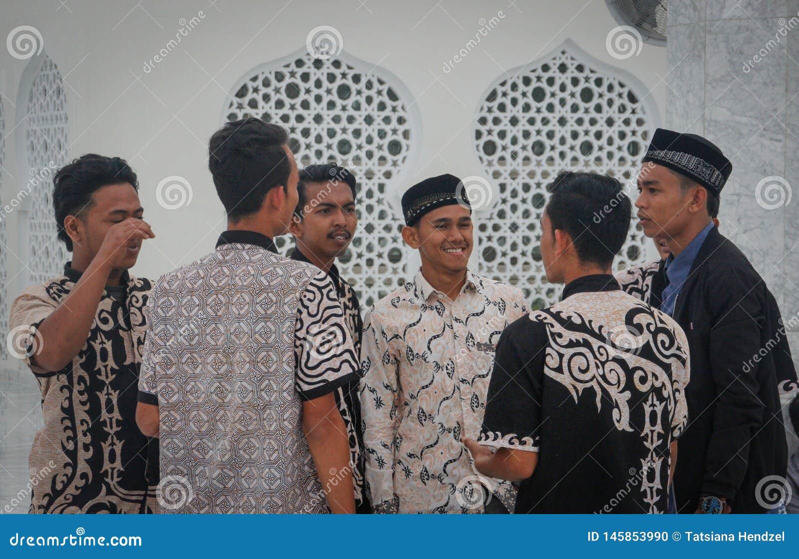 Un grupo de hombres asiáticos musulmanes jovenes en camisas hermosas se está colocando cerca de las paredes de la mezquita