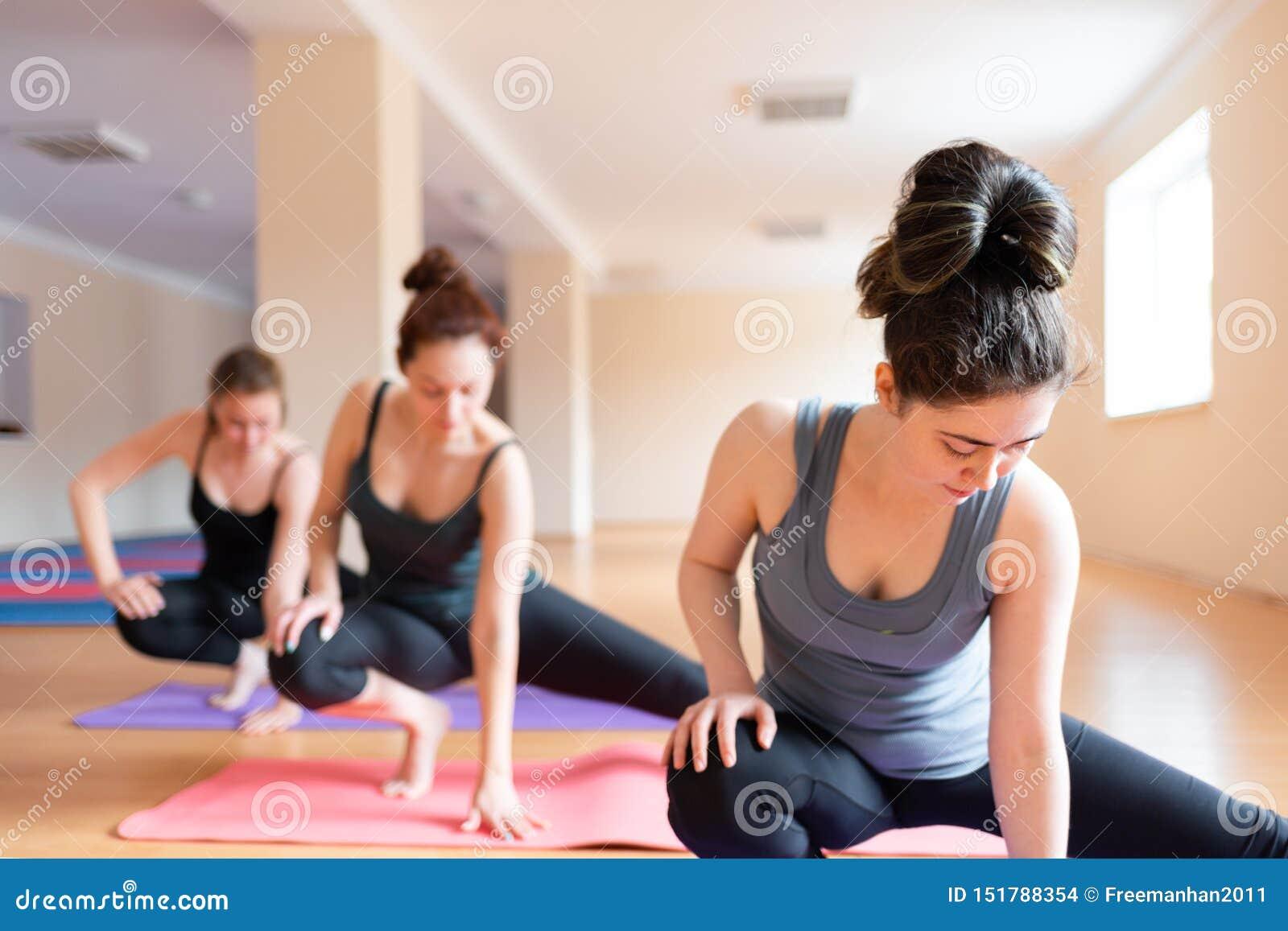 Un grupo de mujeres jovenes que hacen yoga en la sala de clase El concepto de práctica de los deportes, de los aeróbicos y de la