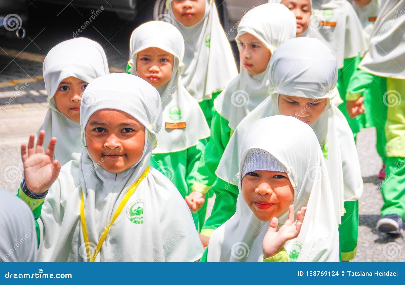 Un grupo de pequeñas muchachas asiáticas de la escuela primaria en los hijabs blancos