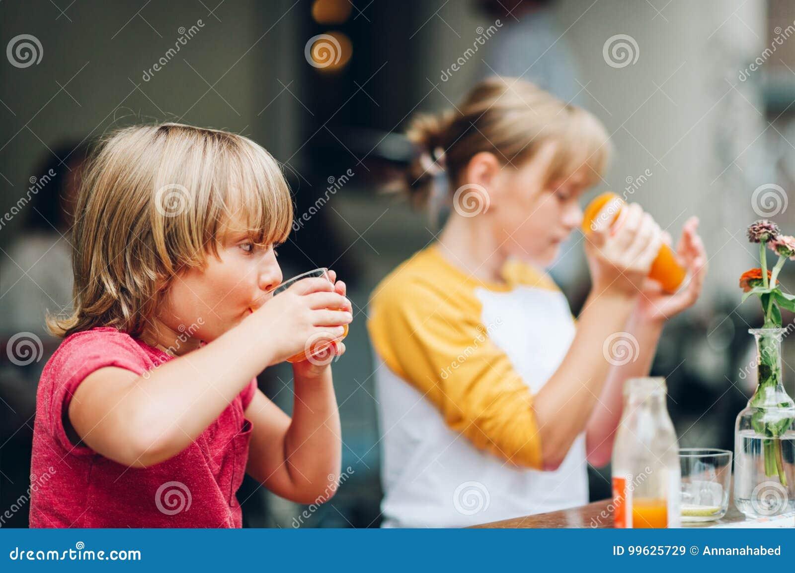 Un gruppo di due bambini divertenti che hanno bevanda in caffè