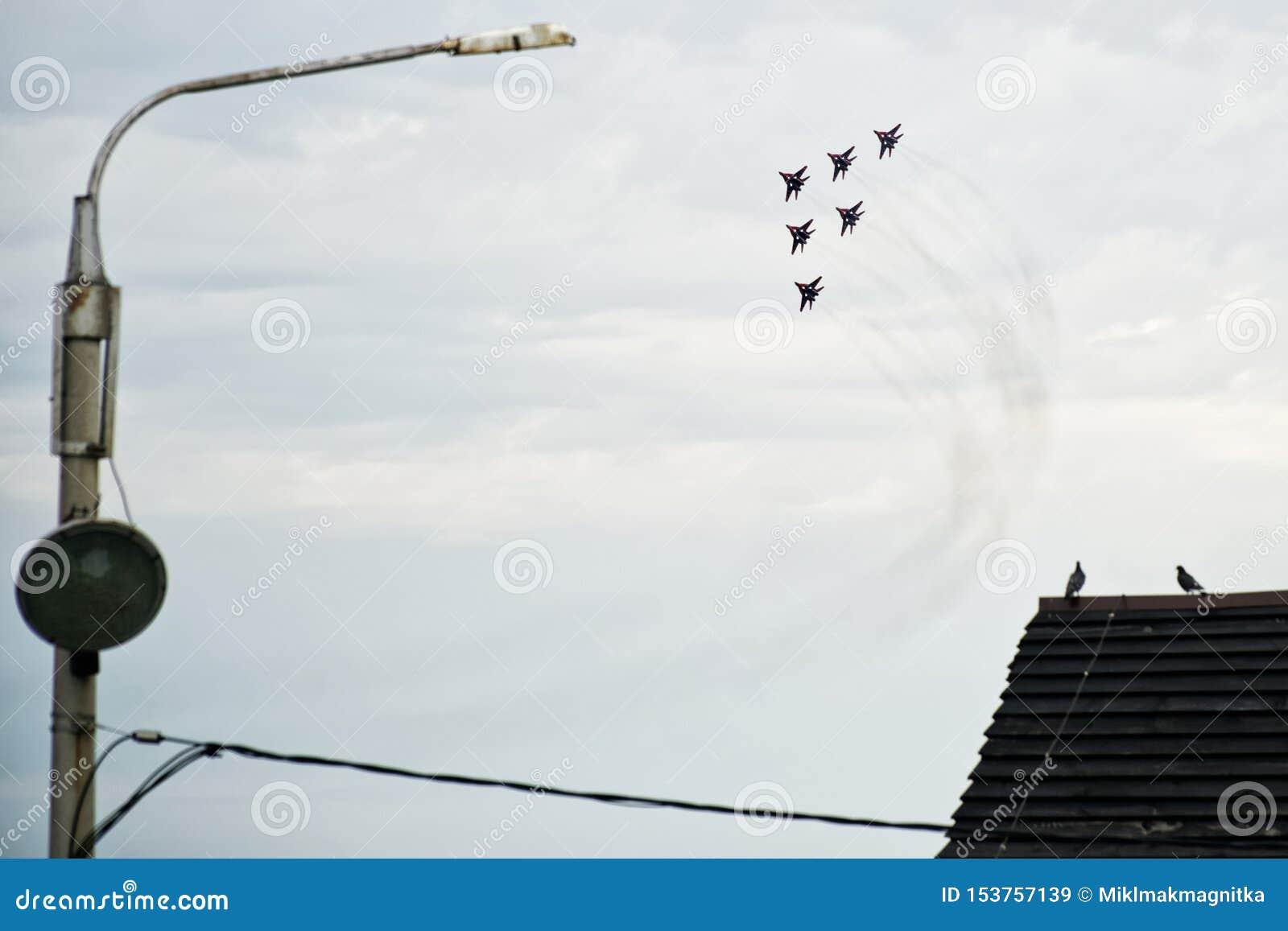 Un gruppo di fulcro-Un russo MIG 29 del combattente 6 in volo sopra la città