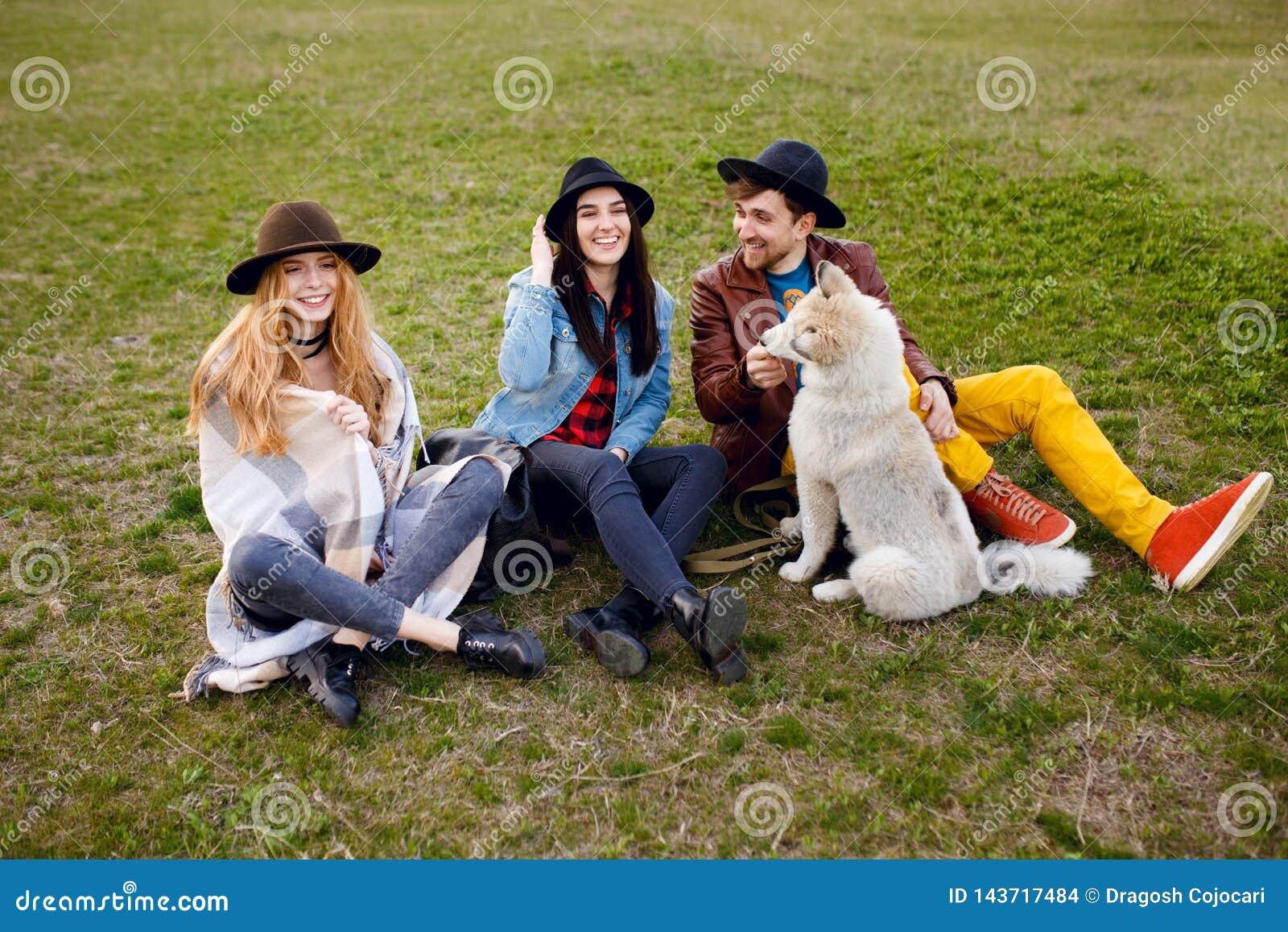 Un gruppo di giovani e sorridenti passa il tempo insieme al loro cane del husky, sedentesi sull erba, fondo della natura