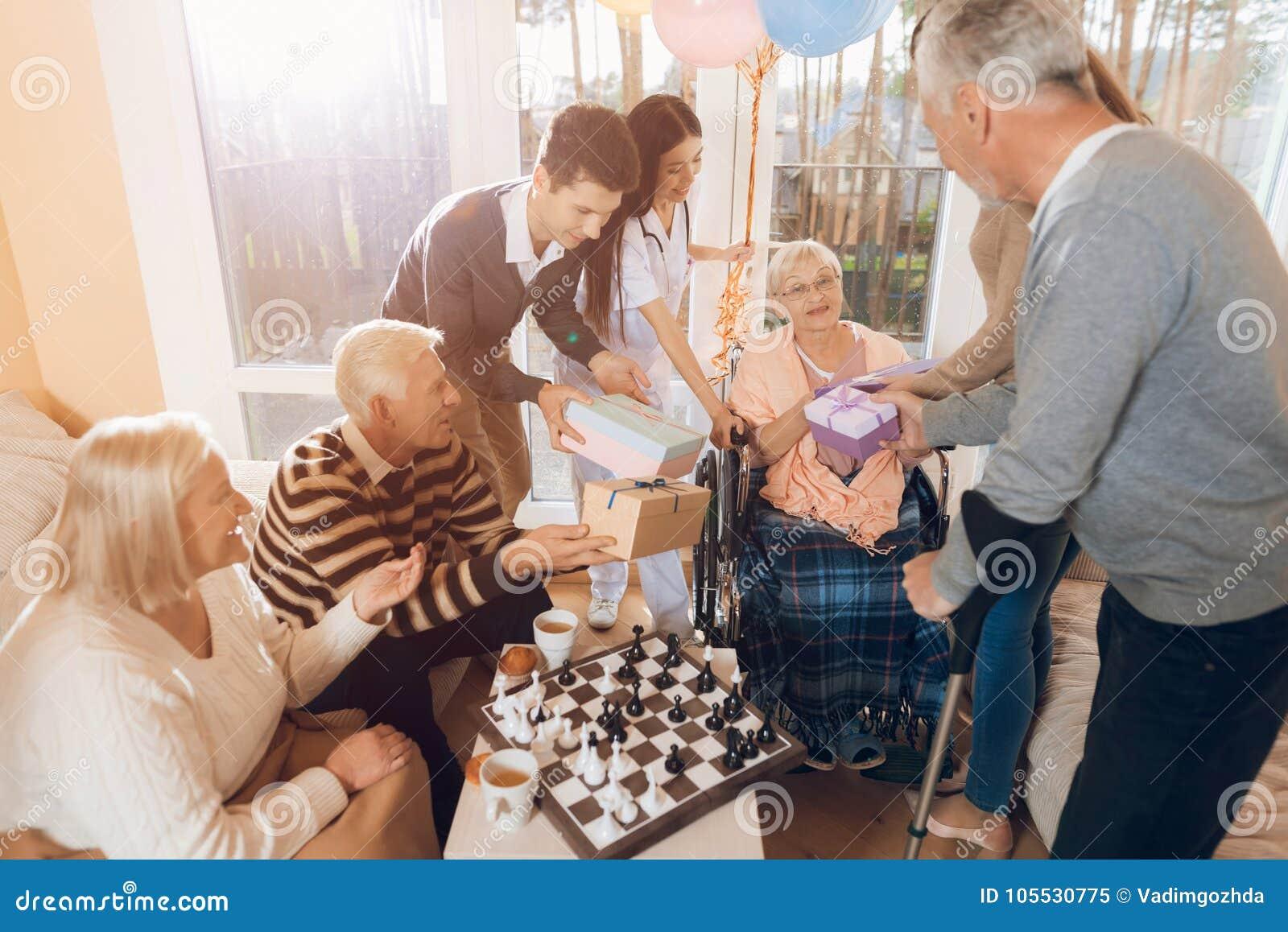 Un gruppo di giovani ed anziani in una casa di cura si congratula una donna anziana sul suo compleanno