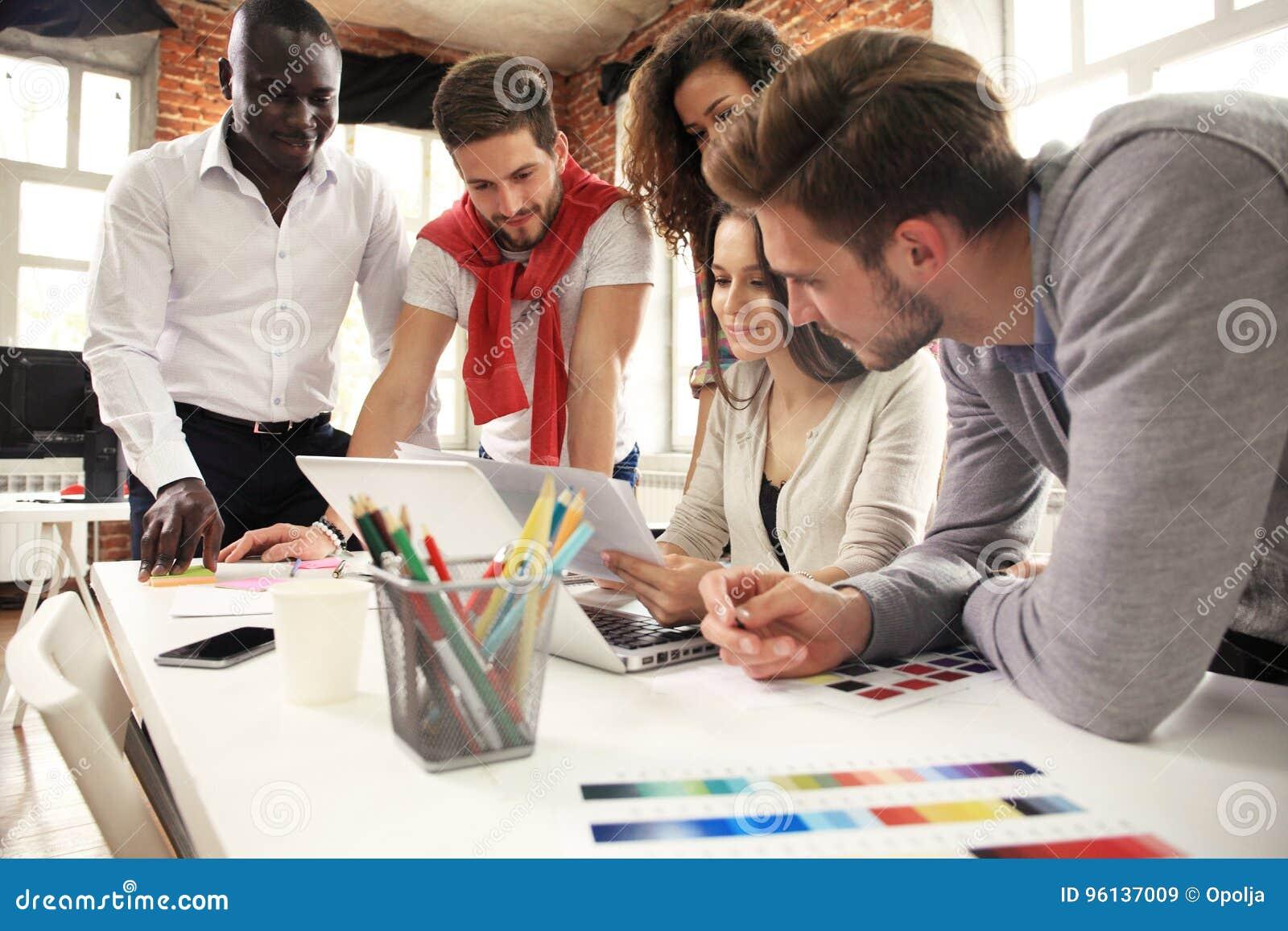 Un gruppo di lampo di genio creativo del lavoratore cinque insieme in ufficio, nuovo stile di area di lavoro, scena felice della
