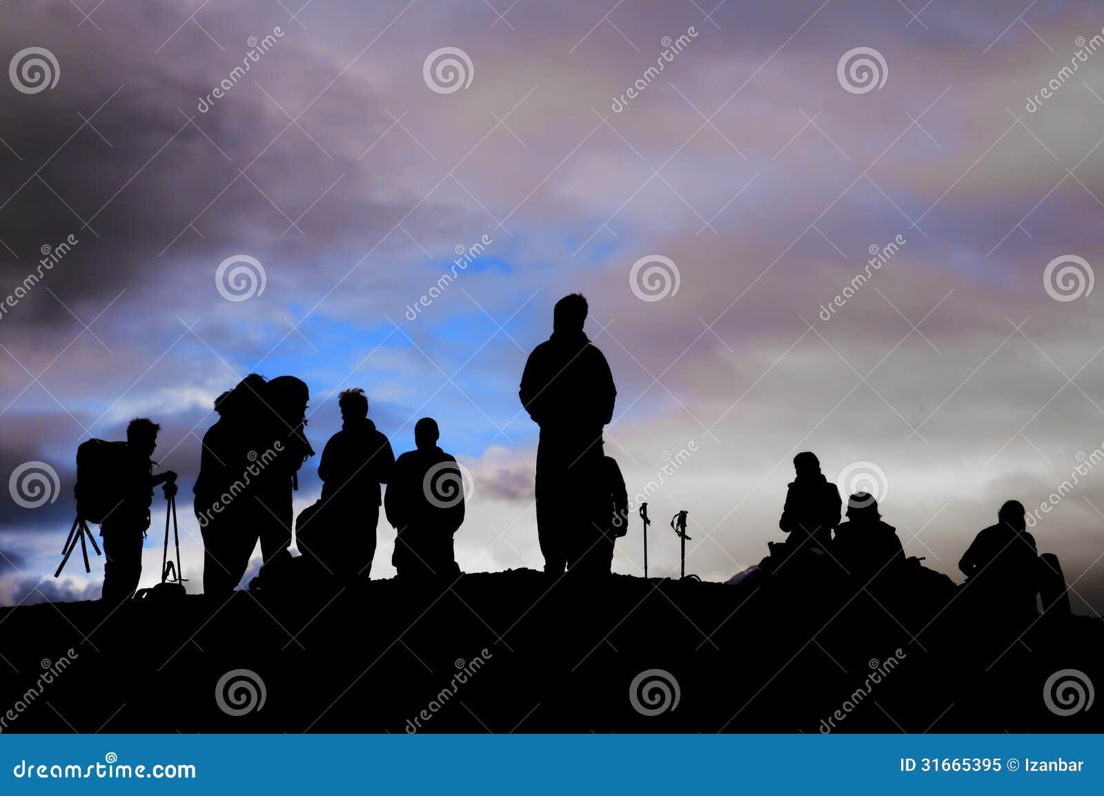 Un gruppo di siluetta nera dei trekkers nei precedenti del cielo nuvoloso