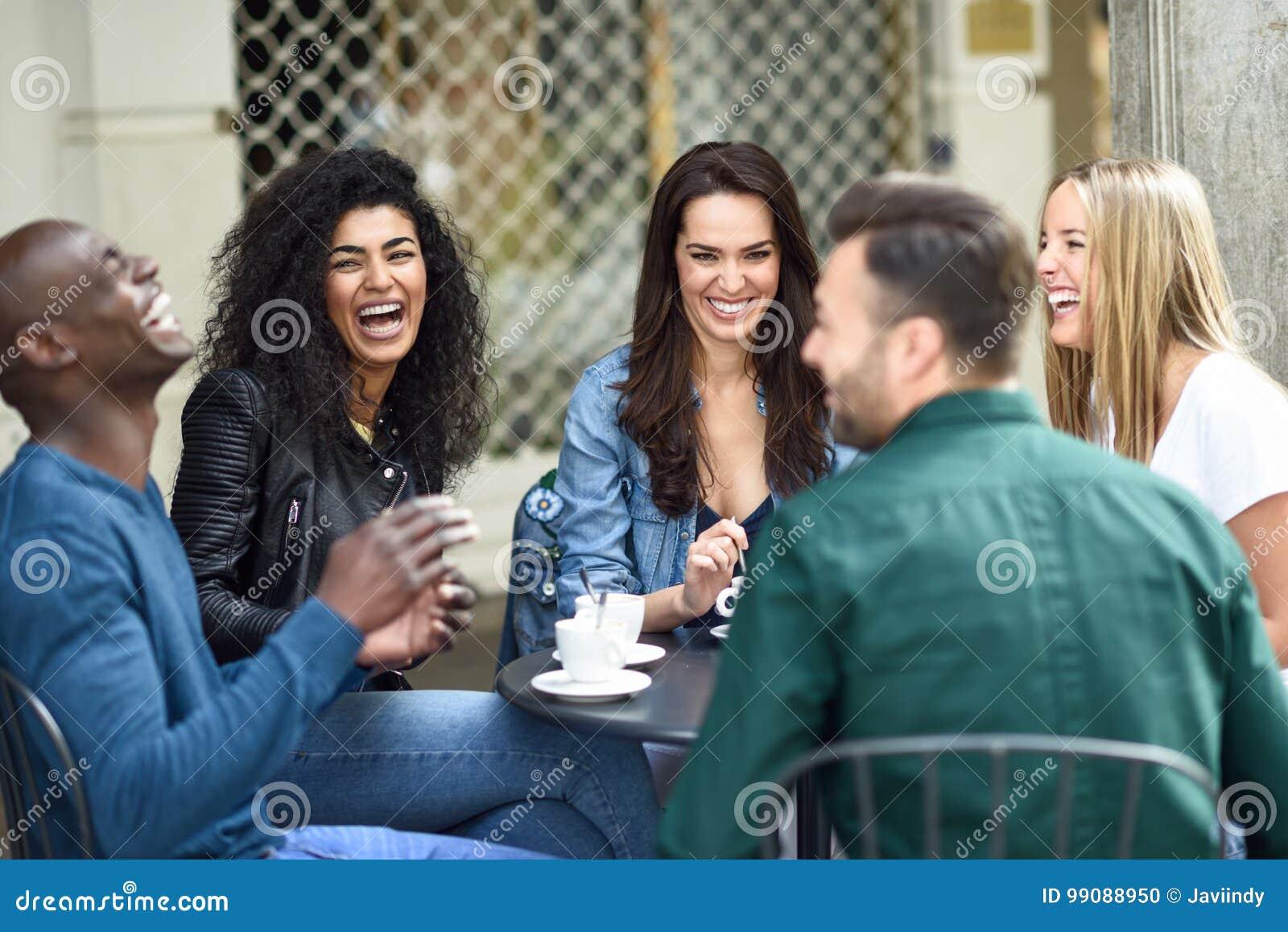 Un gruppo multirazziale di cinque amici che mangiano un caffè insieme
