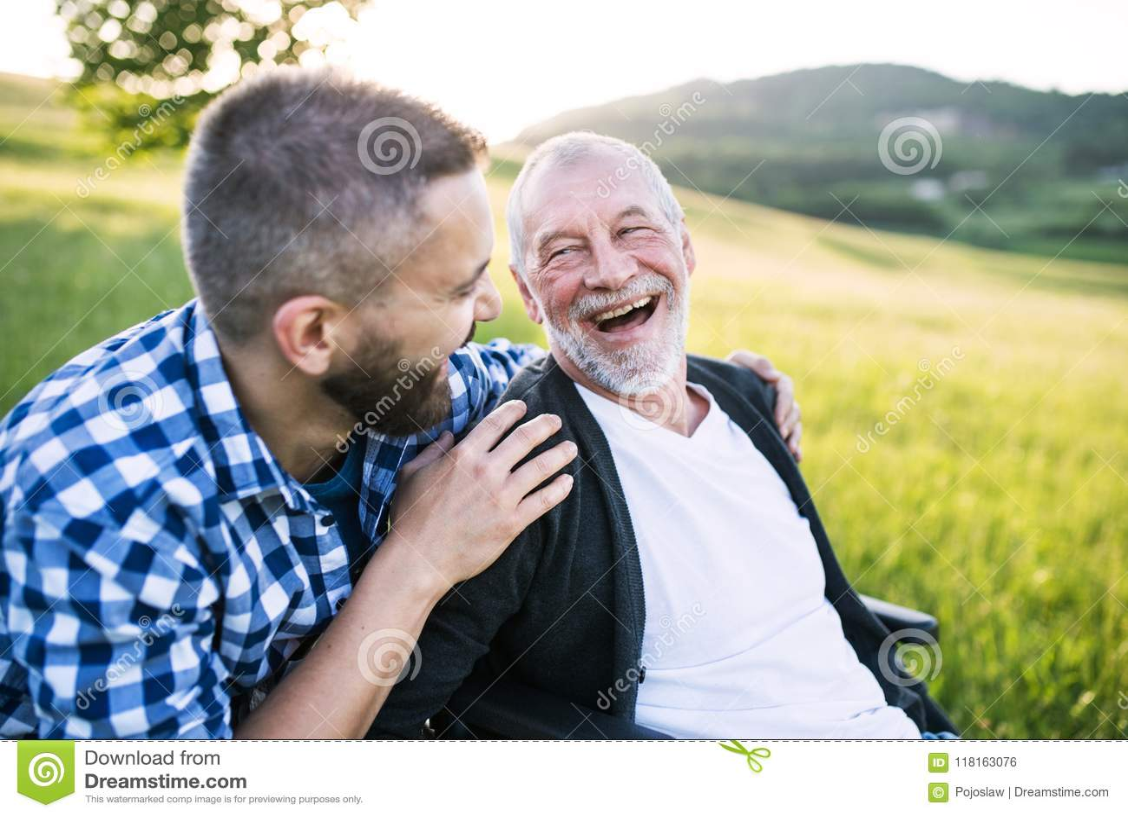 Un hijo adulto del inconformista con el padre mayor en silla de ruedas en un paseo en naturaleza en la puesta del sol, riendo