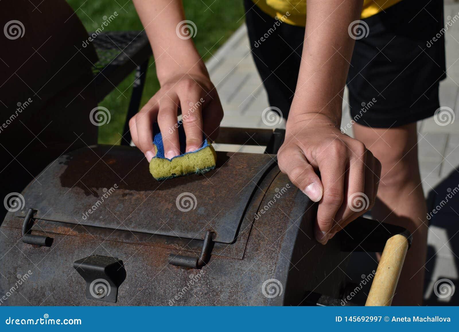 Un hombre adulto que limpia la parrilla al aire libre