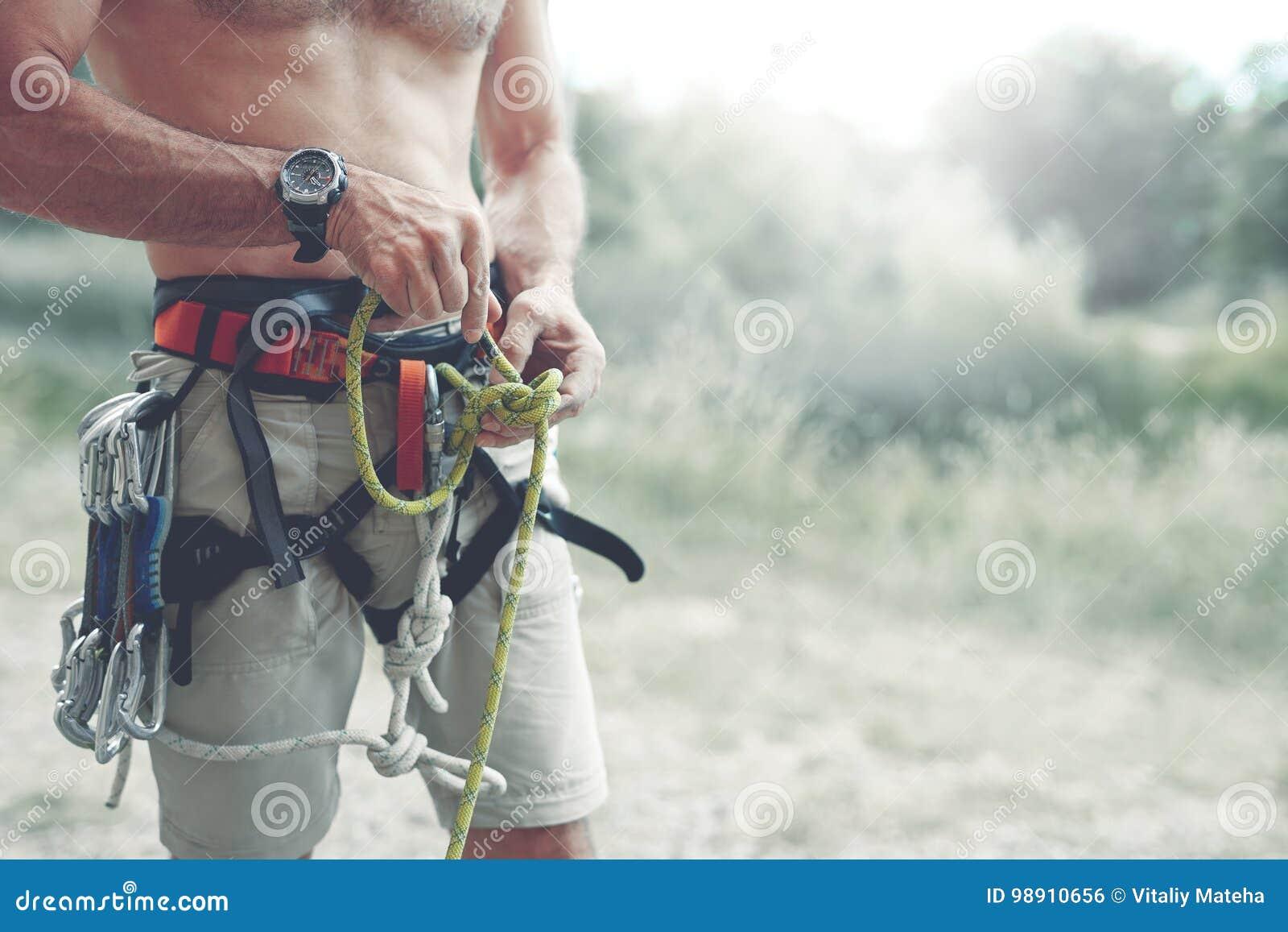 Un hombre anuda un nudo en un arnés que sube