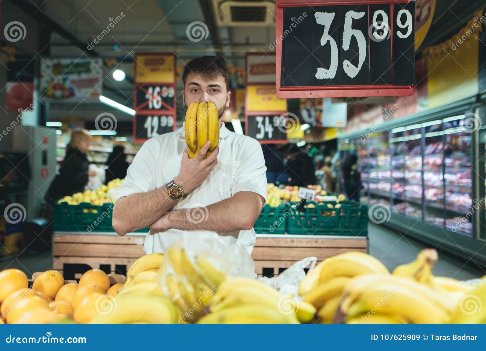 Un hombre con los plátanos en sus manos presenta en un supermercado al hacer compras El comprador compra la fruta en la tienda