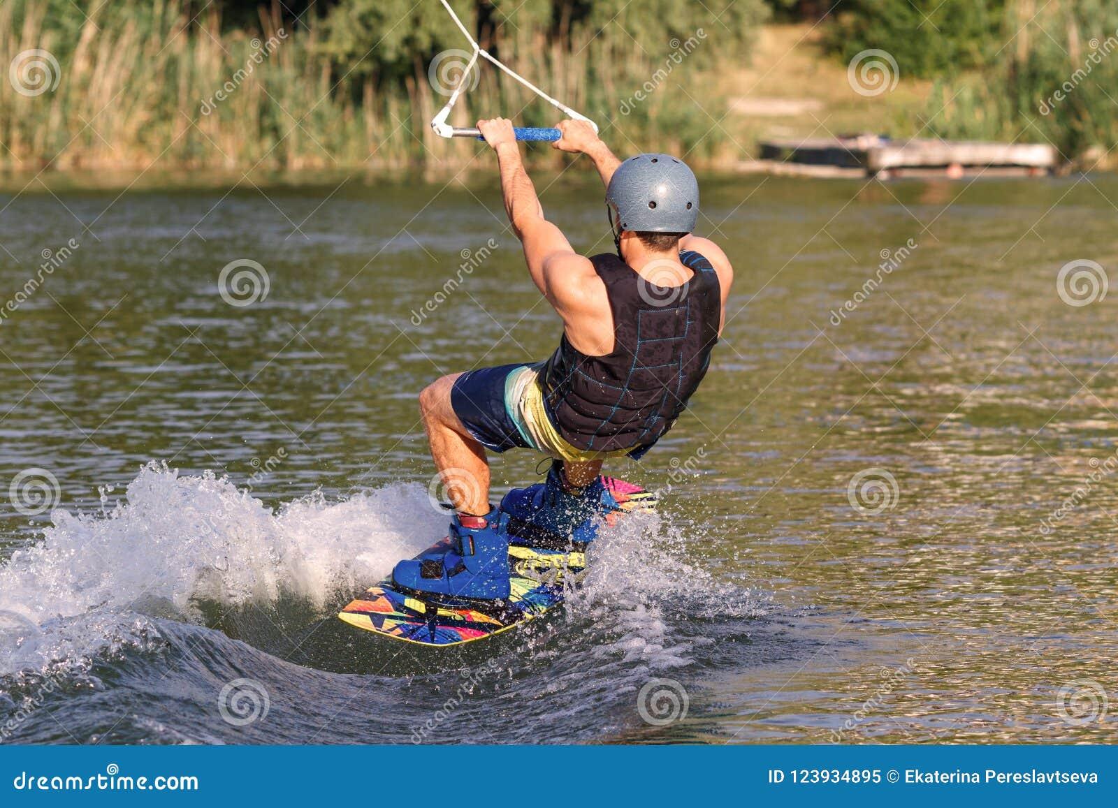 Un hombre contratado a wakeboard en el lago realiza saltos