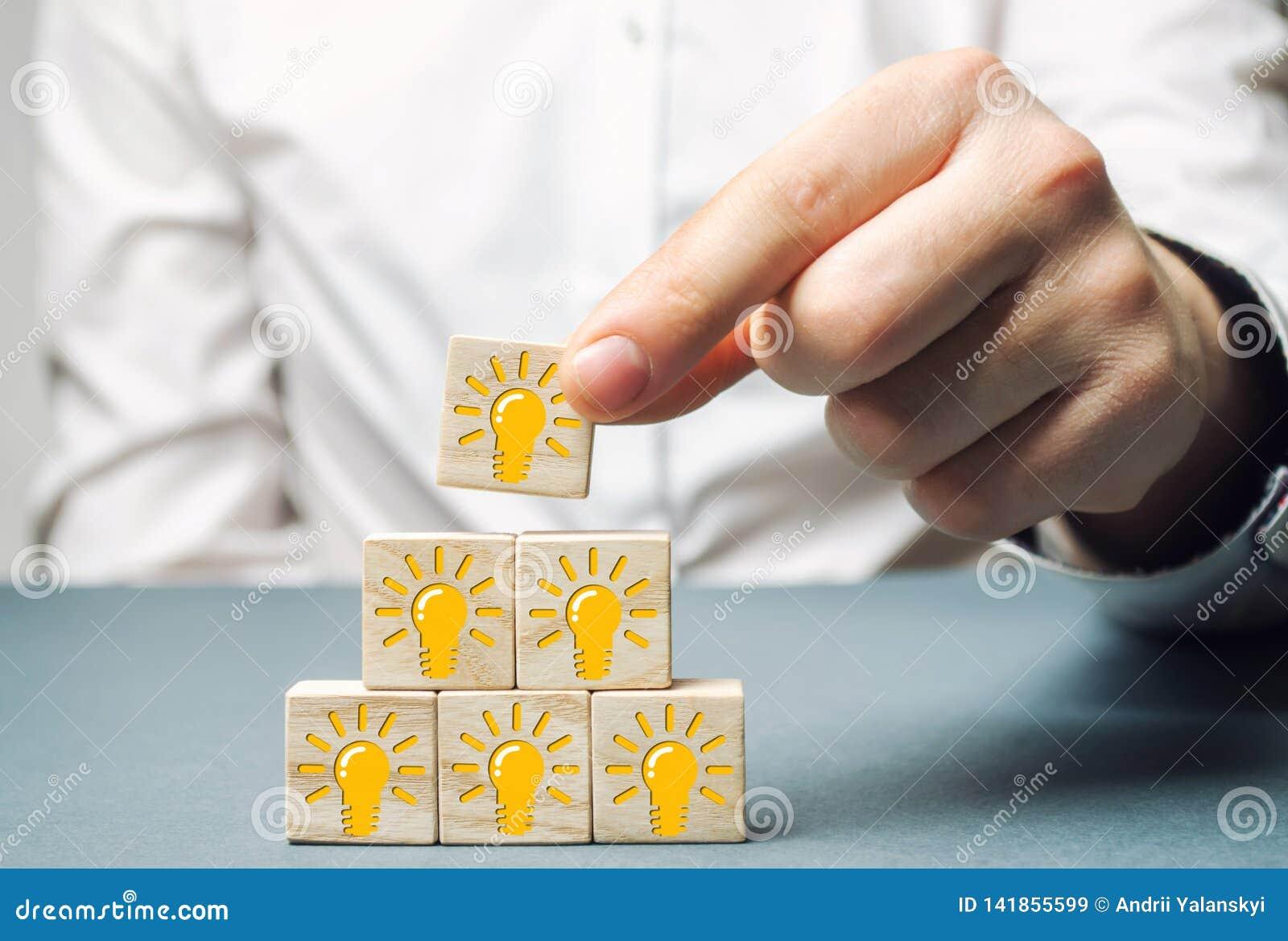 Un hombre de negocios pone bloques de madera con una bombilla de una idea o de una inspiración Generación de ideas innovadoras de