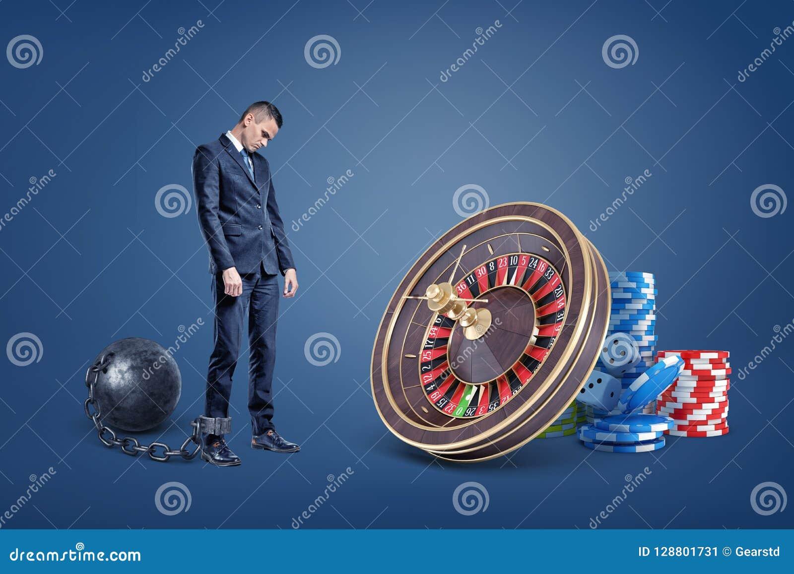 Un hombre de negocios triste encadenado a los soportes de una bola del hierro cerca de una ruleta del casino y de pilas del micro