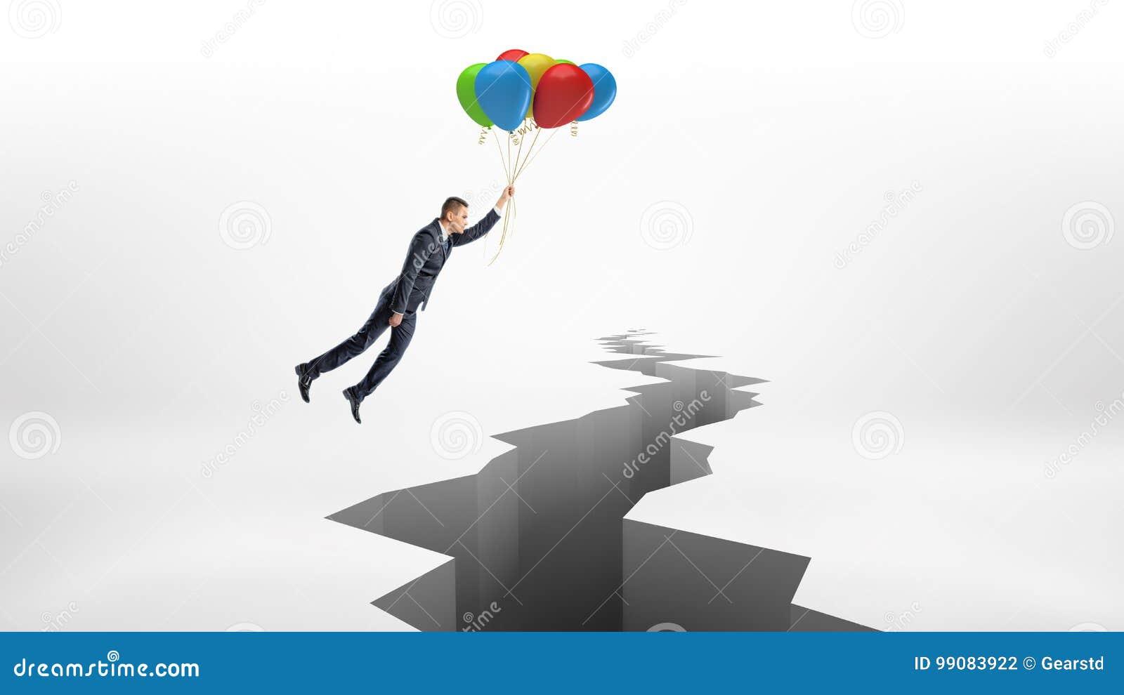 Un hombre de negocios vuela sobre una grieta enorme en la superficie blanca mientras que sostiene un manojo de globos coloridos