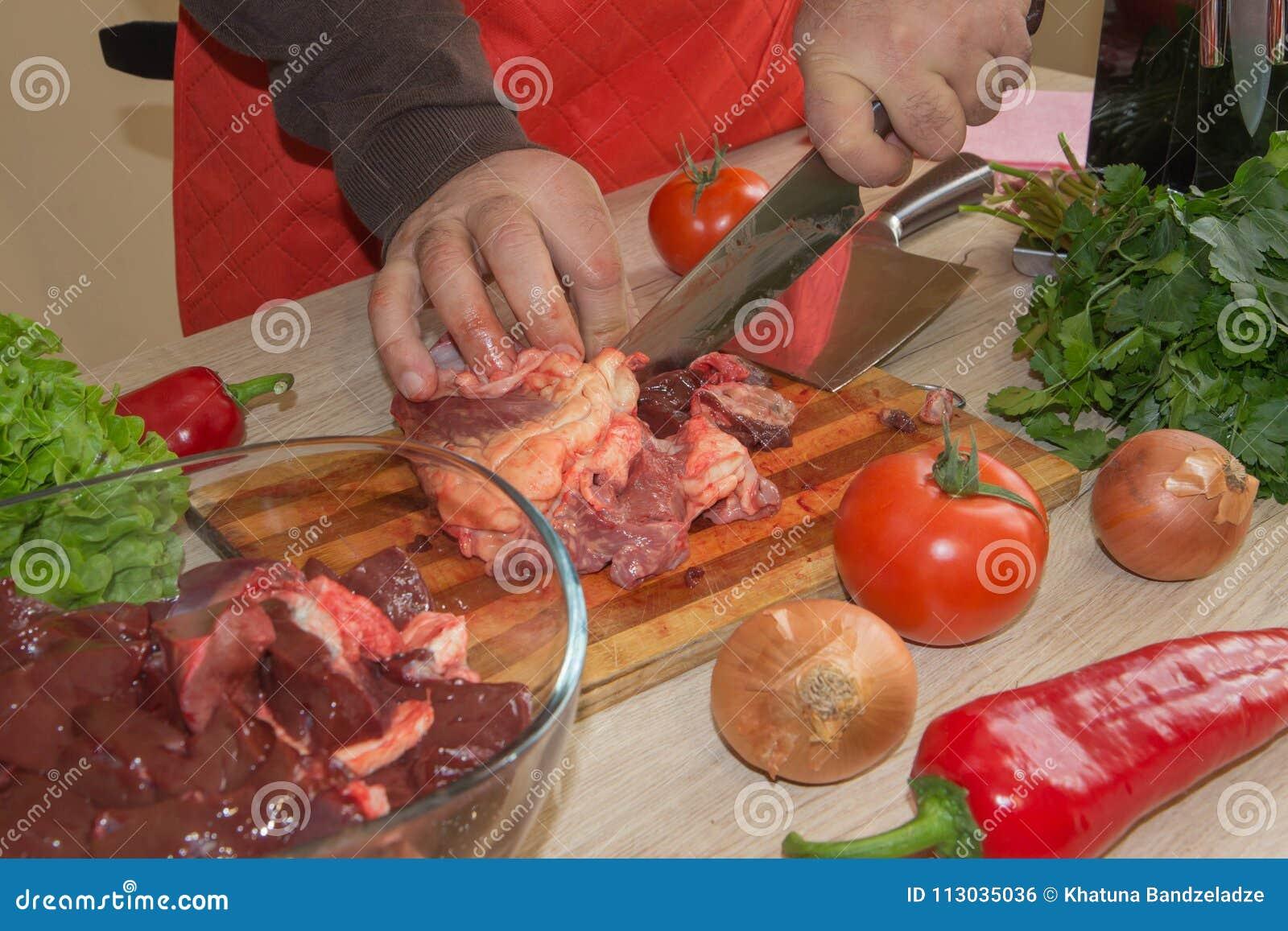 Un hombre en un delantal de la cocina, carne en un tablero y una tabla de madera, un cuchillo y verduras
