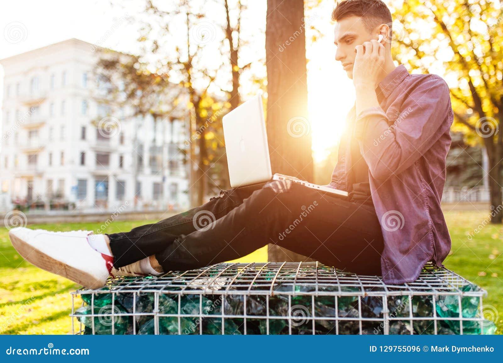 Un hombre en ropa casual se sienta en un banco, trabaja con un ordenador portátil y
