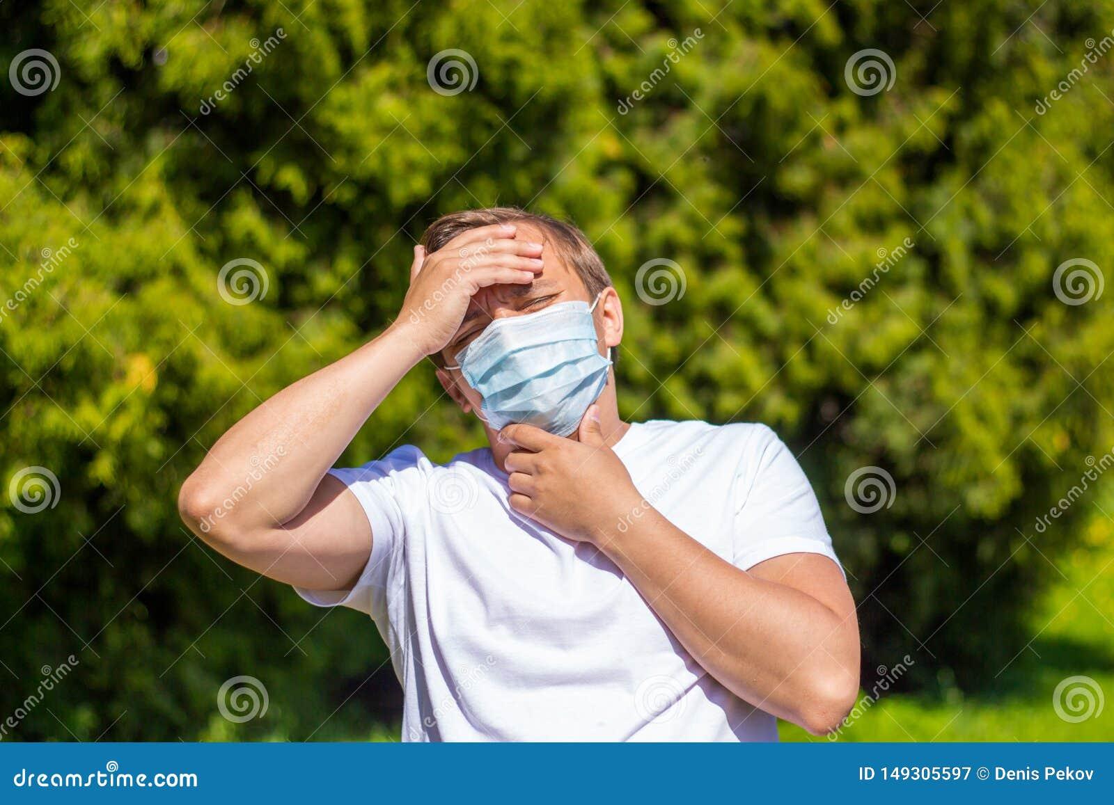 Un hombre en una m?scara de la alergia, en una camiseta blanca, soportes en el parque