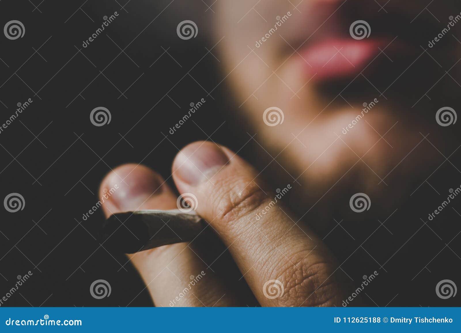 Un hombre fuma la mala hierba del cáñamo, una junta y un encendedor en sus manos Humo en un fondo negro Conceptos de marijuana mé
