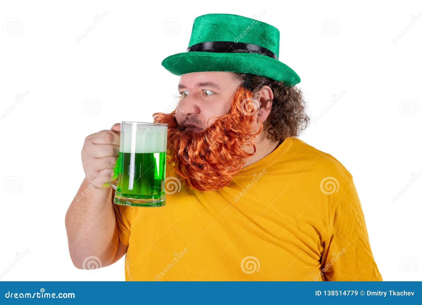 Un hombre gordo feliz sonriente en un sombrero del duende con la cerveza verde en el estudio Él celebra St Patrick