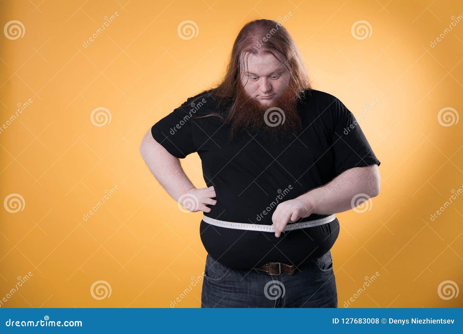 Un hombre gordo grande mide sus tamaños grandes con una cinta