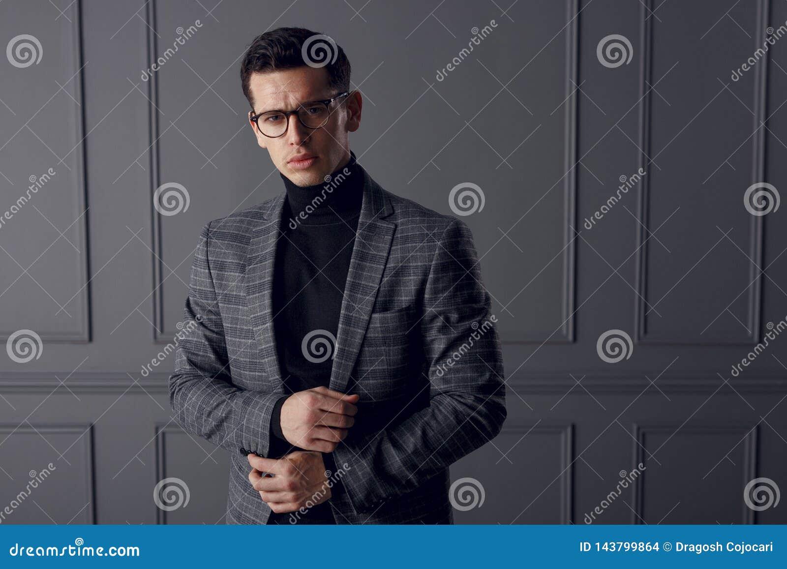 Un hombre hermoso en una chaqueta gris y un cuello alto negro, colocándose en frente y pareciendo confiados, en fondo gris de la