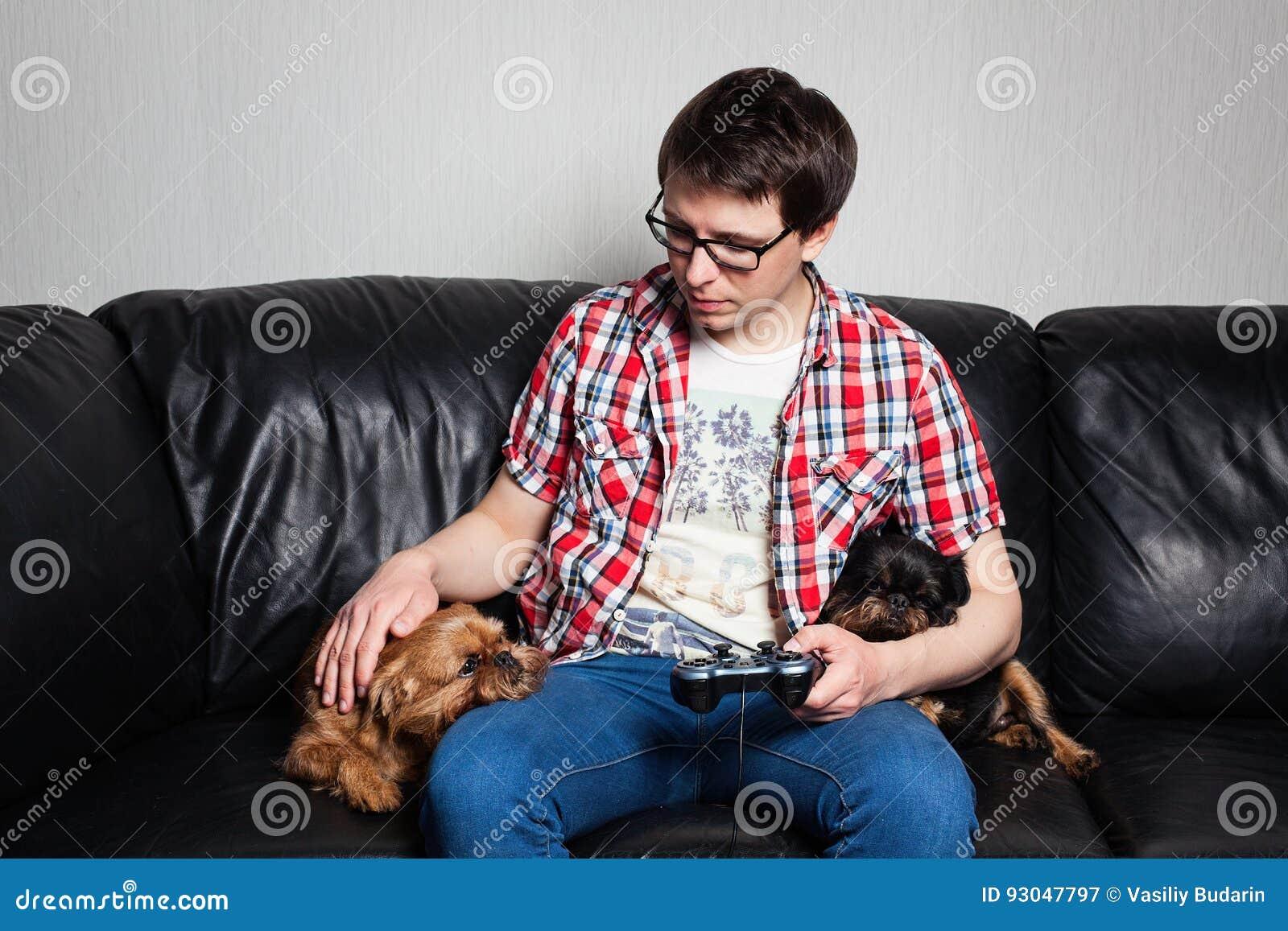 Un hombre joven en una camisa roja y tejanos se sienta en casa y juega a los videojuegos así como su perro El individuo llevó una