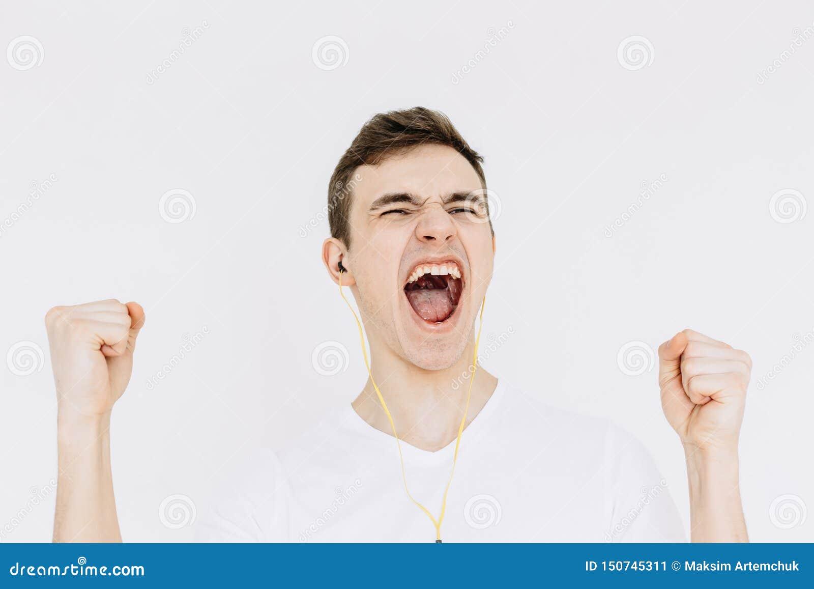 Un hombre joven que grita mientras que escucha la música y aprieta sus puños Fondo blanco aislado