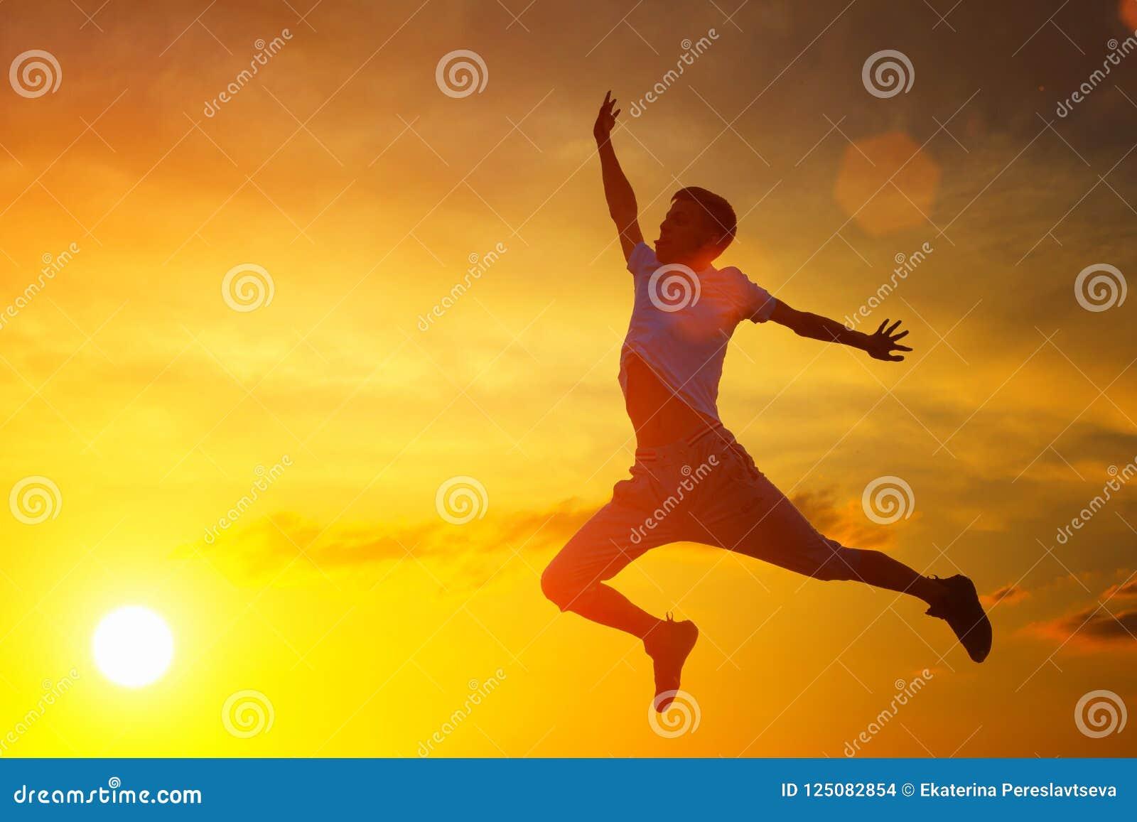 Un hombre joven salta al top en el fondo de la puesta del sol